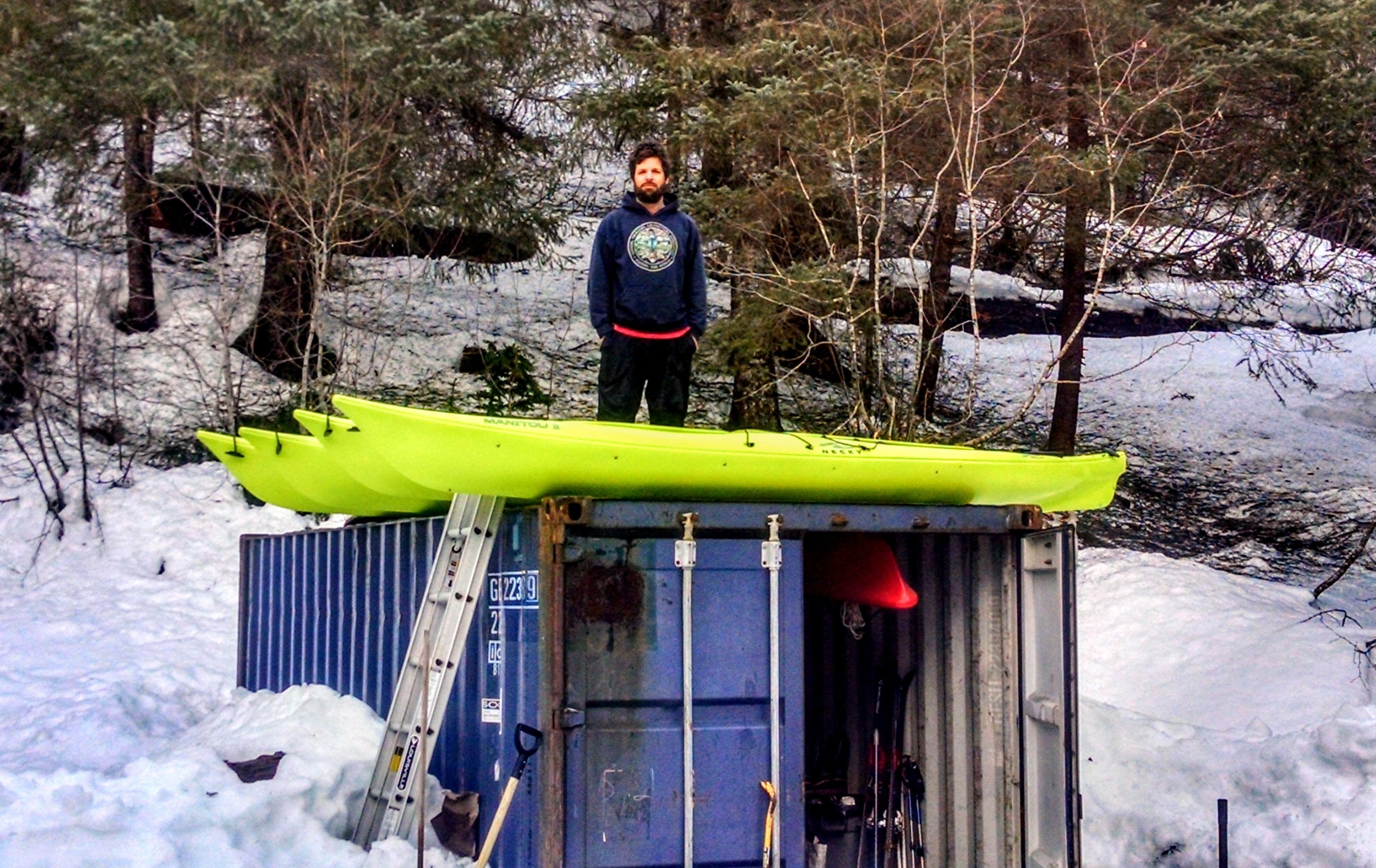 Jason with the new kayaks on top of our storage conex. Our other three kayaks are hanging from the ceiling inside.