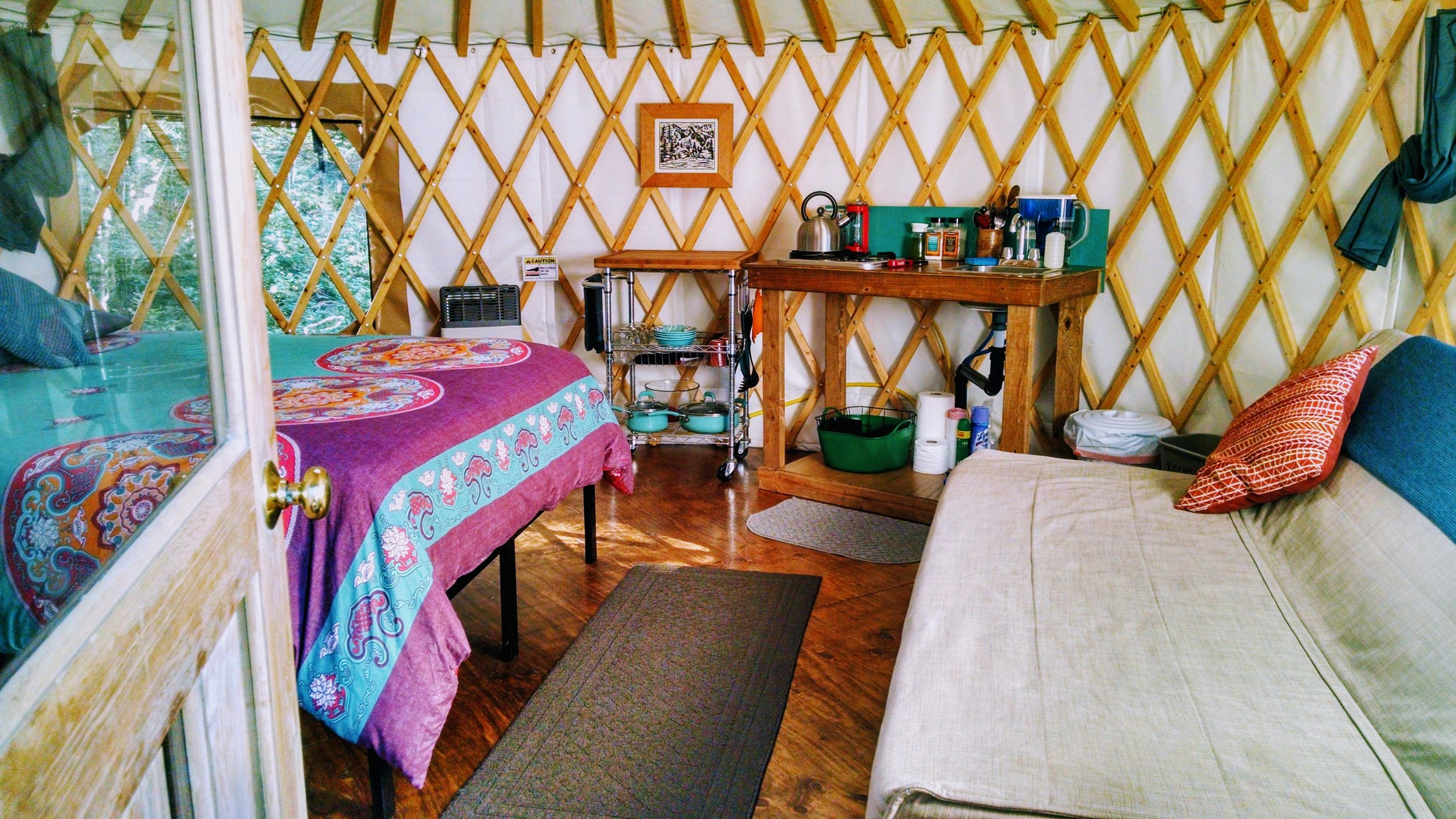 View of the yurt interior: queen memory foam mattress, full size sofa bed, kitchen, rolling cart with cutting board and dishes, heater.