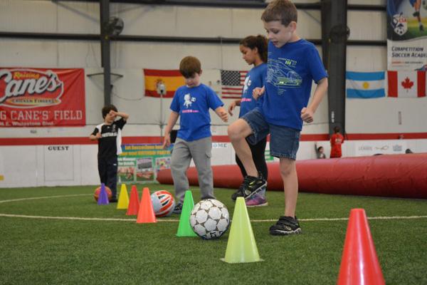 Kids practice weaving soccer balls through cones