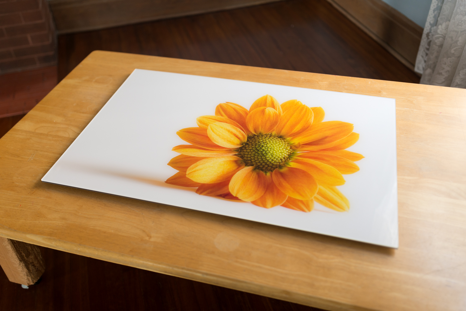Print under acrylic glass, 24X36, top/side view.  A print under acrylic glass is a traditional print that is sealed between a crystal-clear acrylic glass (face) and an aluminum Dibond base. Silicone adhesive is applied around the borders to keep the print airtight and protected.