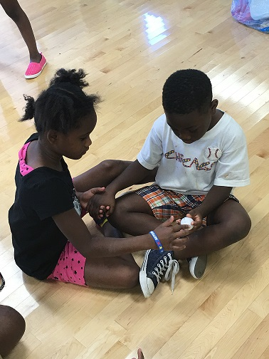 STUDENTS AT SOUTHEAST YMCA DEMONSTRATING A CLOSED CIRCUIT USING JUST THEIR HANDS AND THESE FUN ENERGY BALLS.