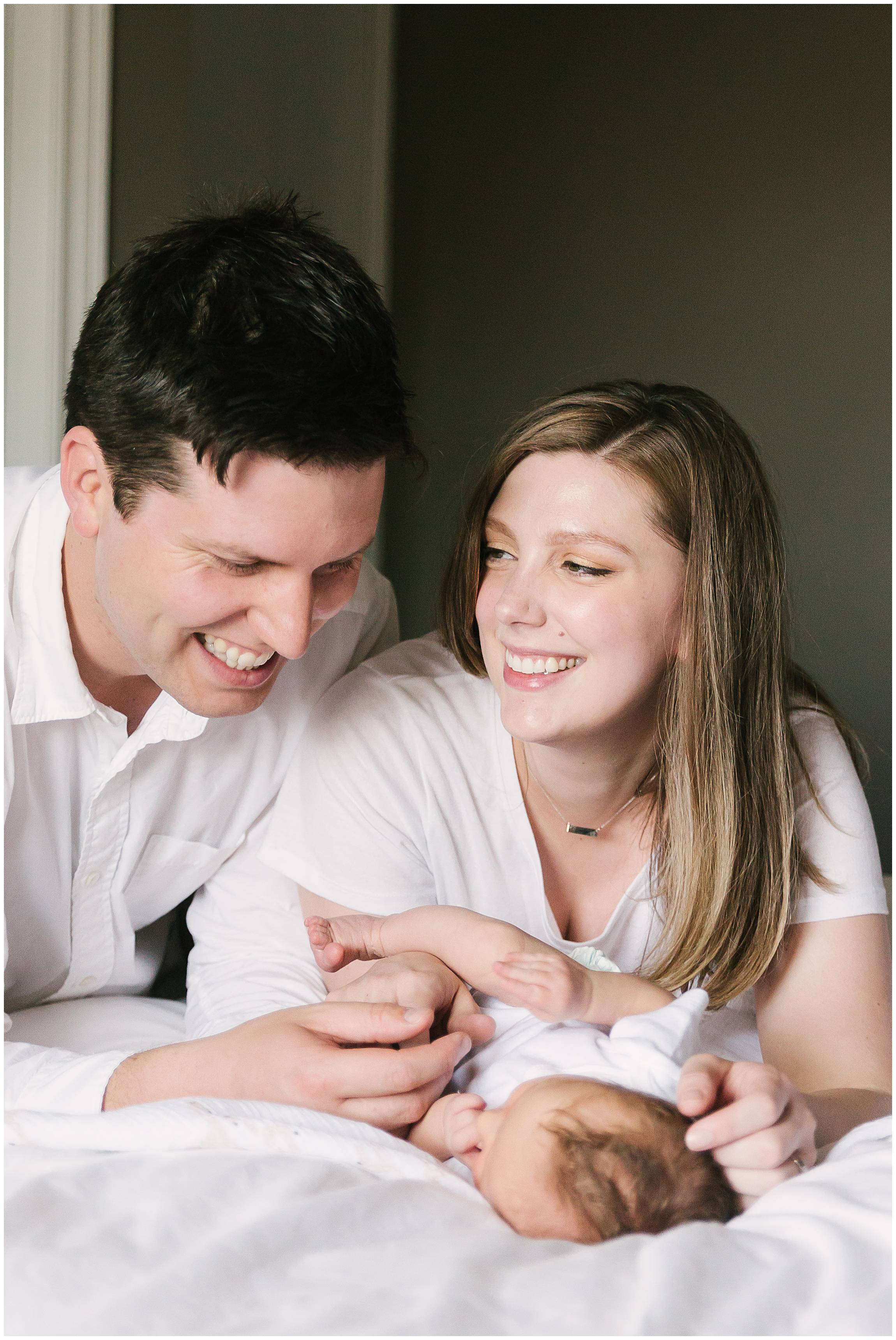 Candid new parents laughing with newborn