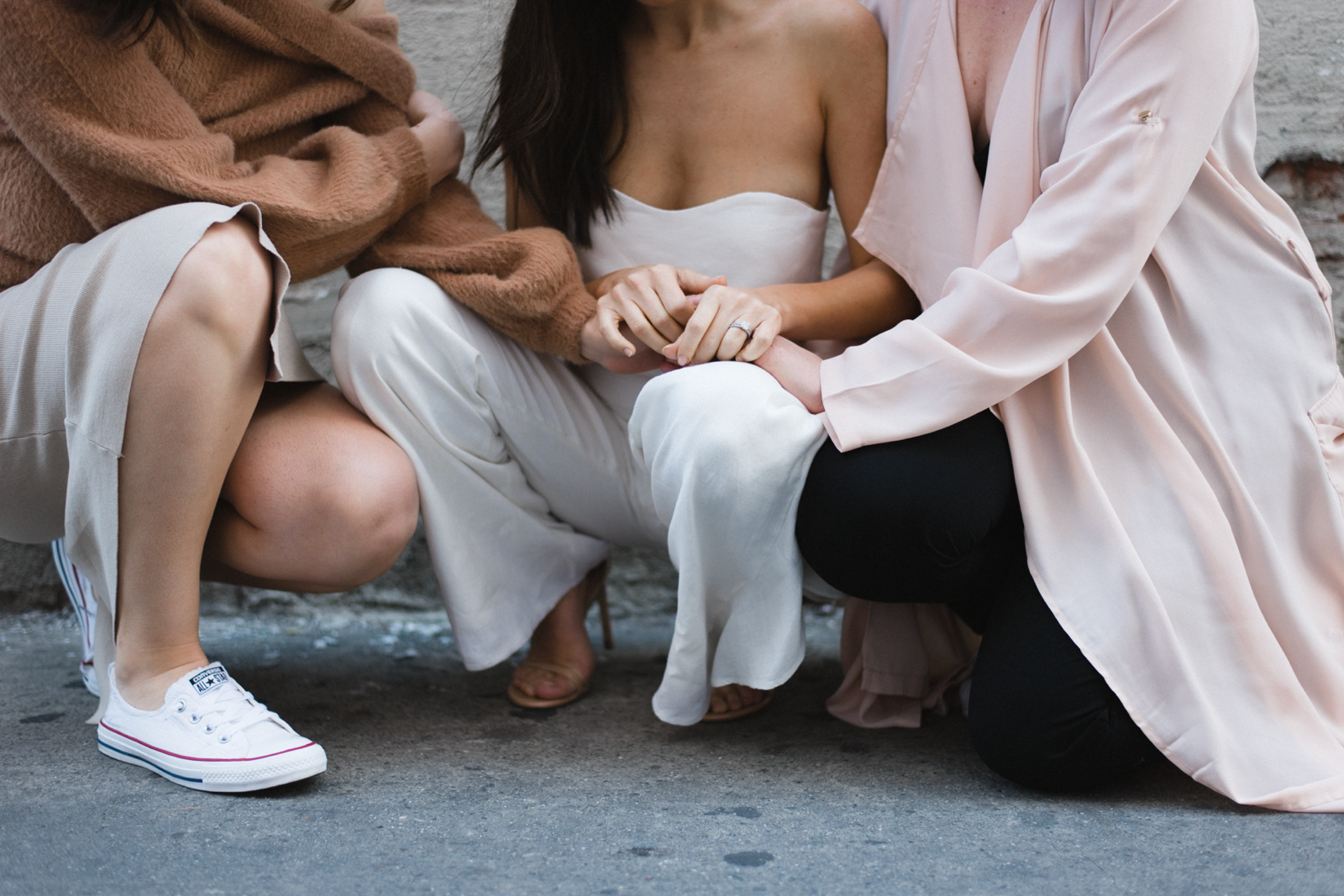 Three mamas in soft, neutral tones kneeling down and holding hands in a rural, downtown setting.