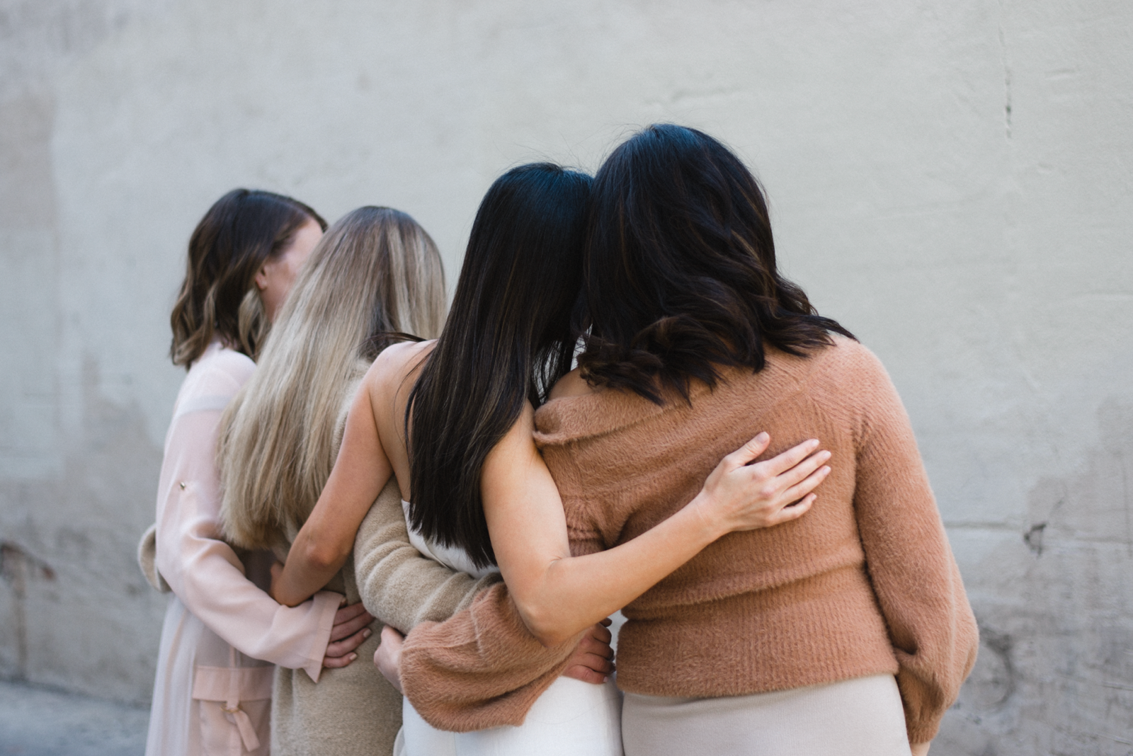 Four happy moms with their backs to the camera and arms wrapped around each other in support and community.