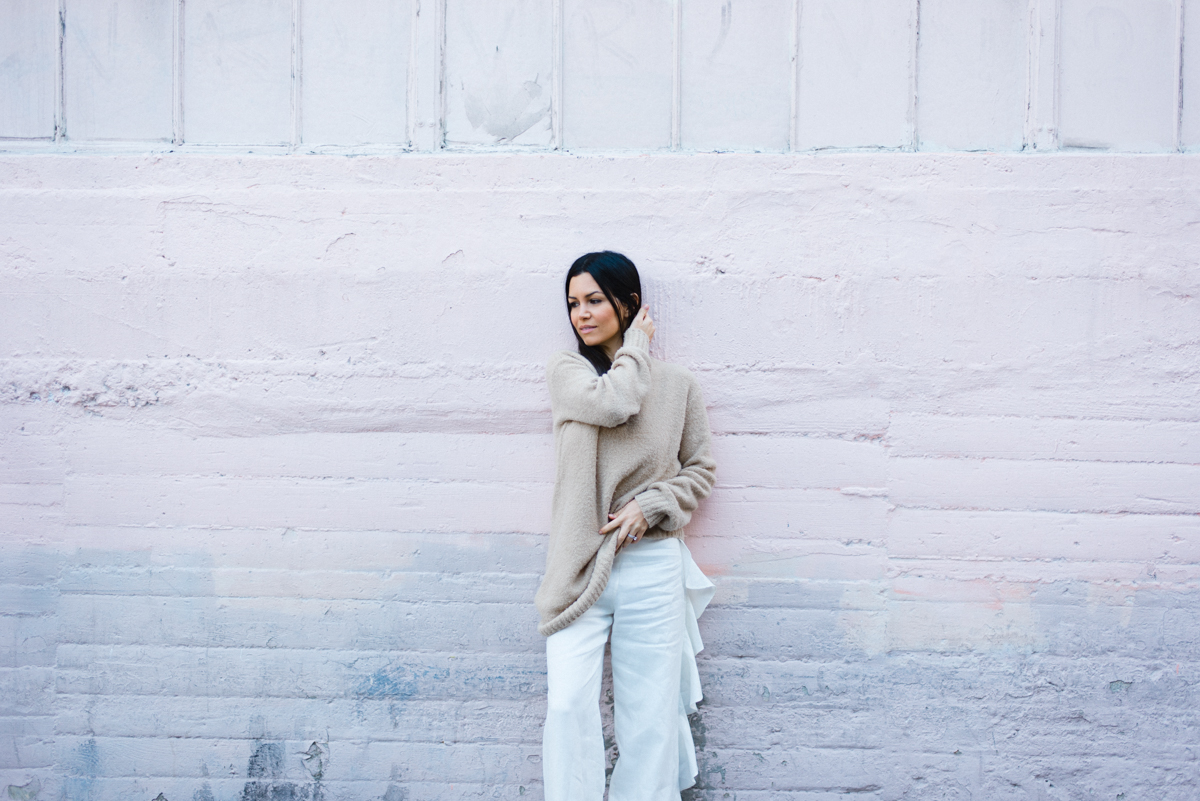 Happy Mom El Abad lounging against a modern concrete wall wearing a chic white jumpsuit and cozy, oversized sweater.