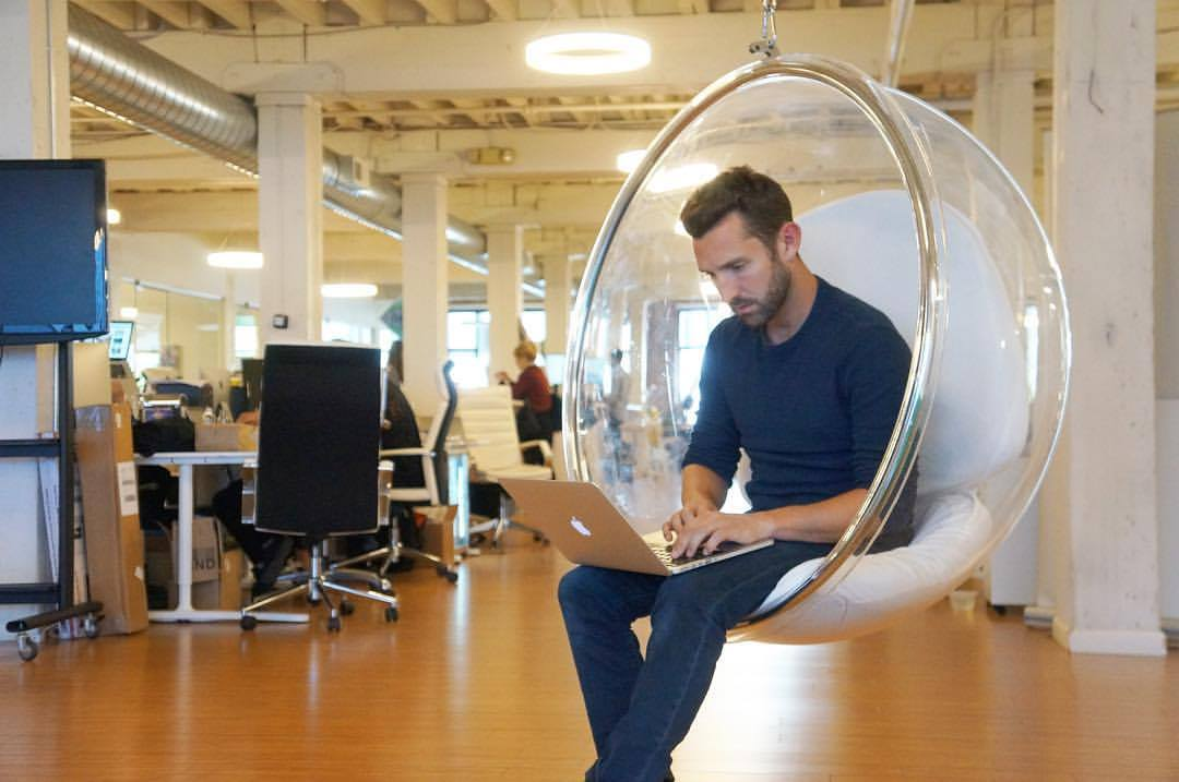 Grant Atkinson of Framework Law Group sitting in a clear, hanging chair while intent at work on his laptop.