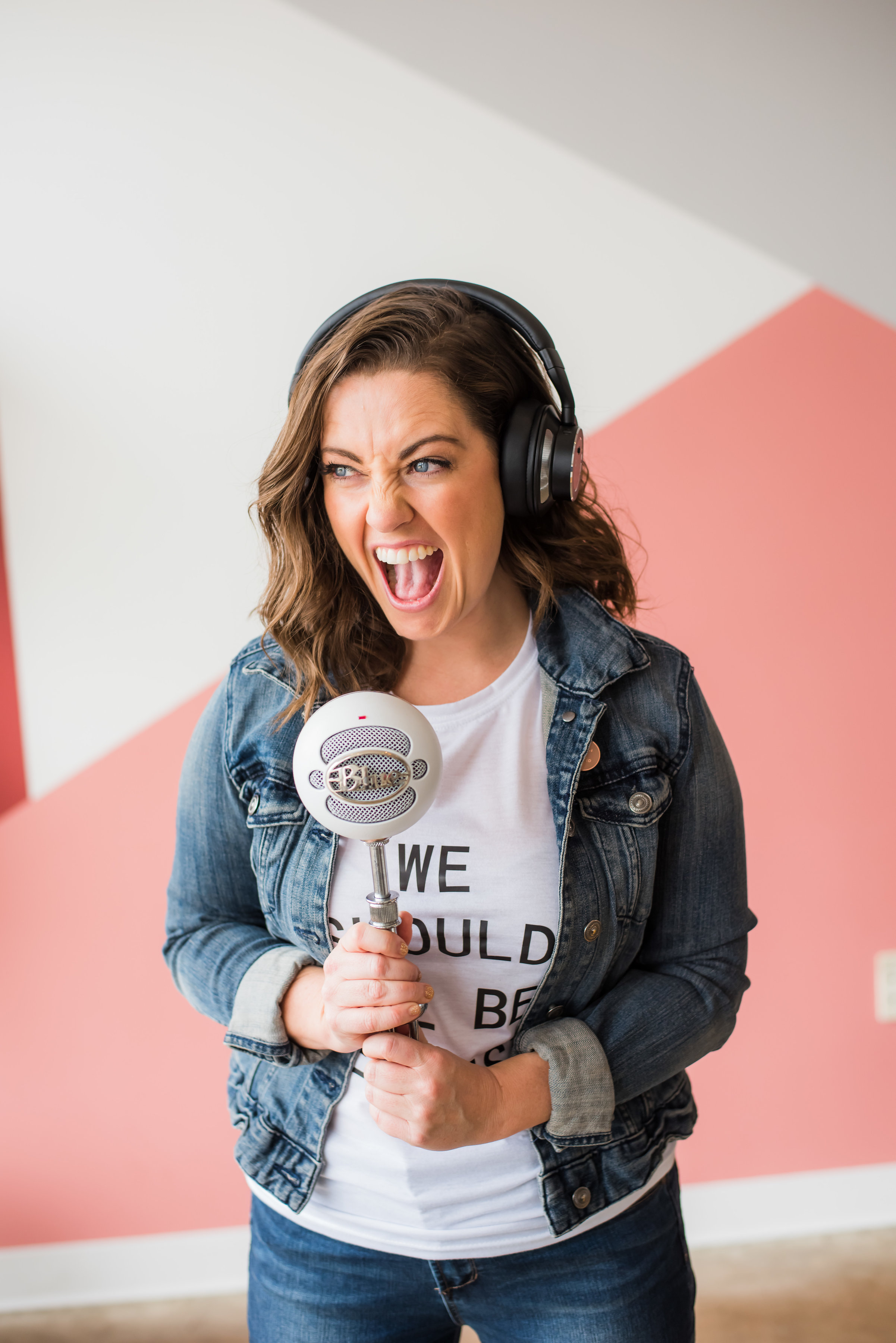 Baily Hancock wearing headphones and shouting playfully into a large microphone