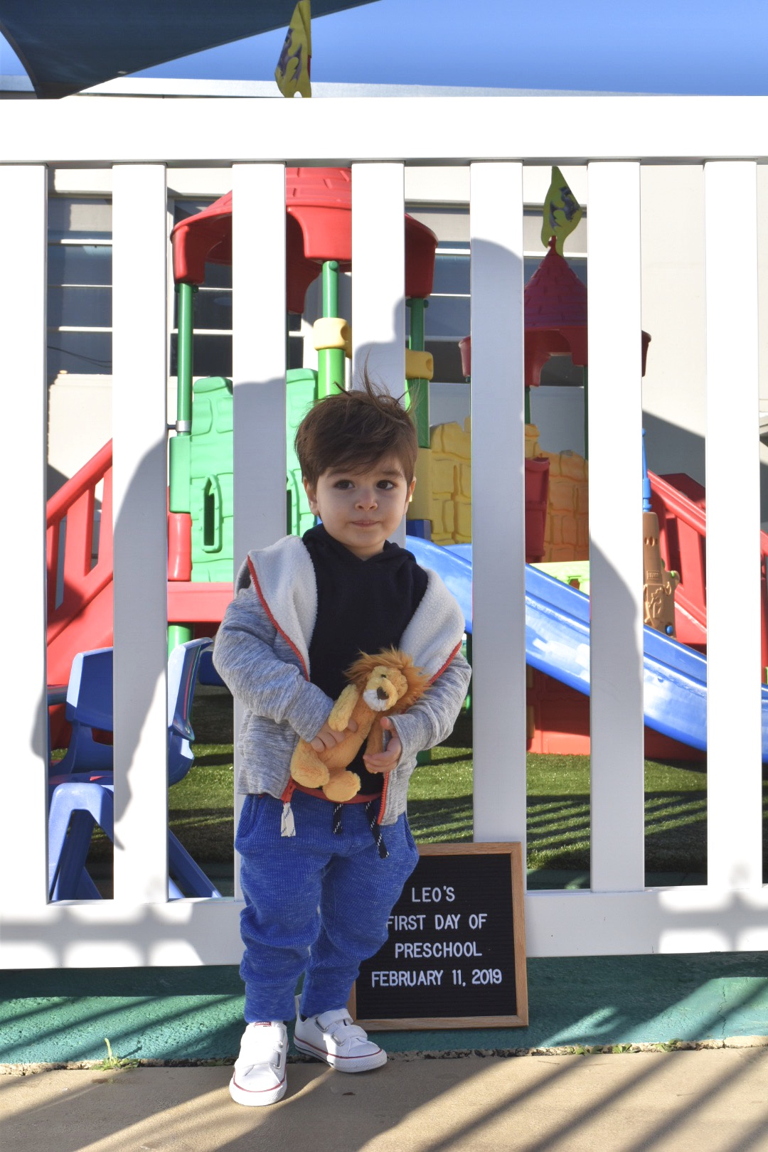 New preschooler holding toy lion while posing with letter board by playground.