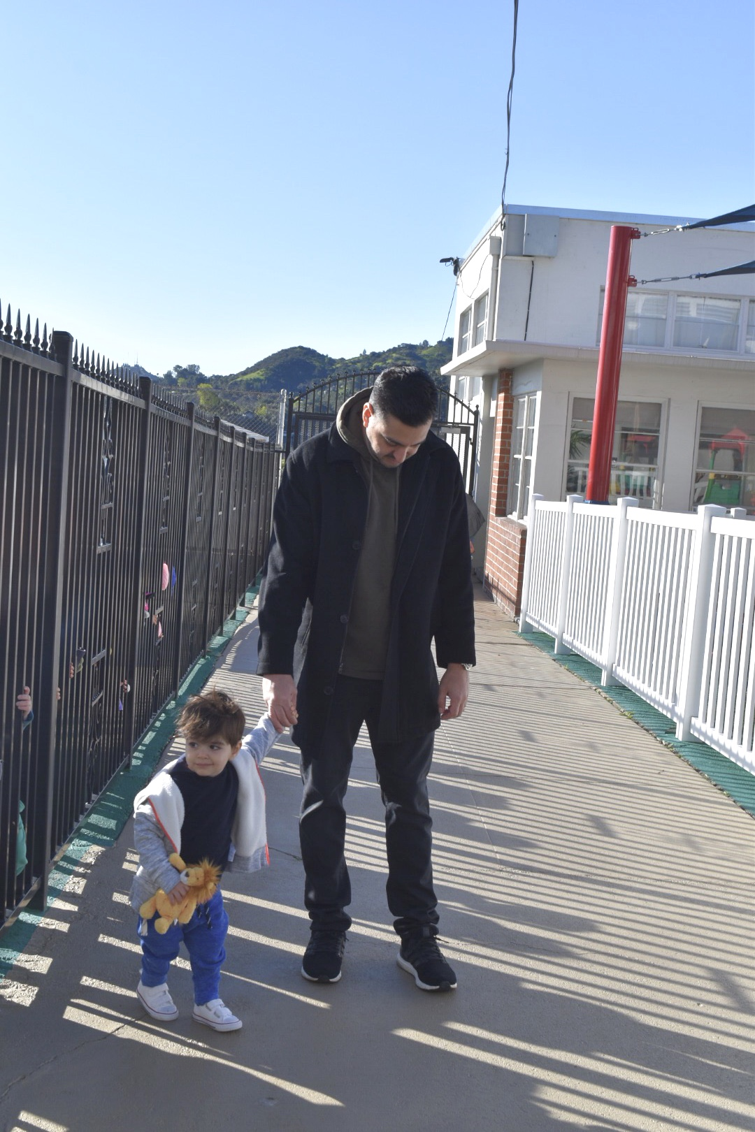 Daddy and son walking to preschool for his first day.