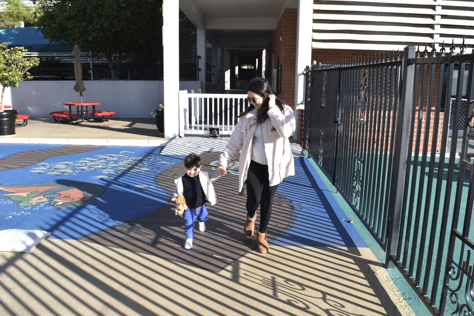 Mama and son walking to preschool for his first day.