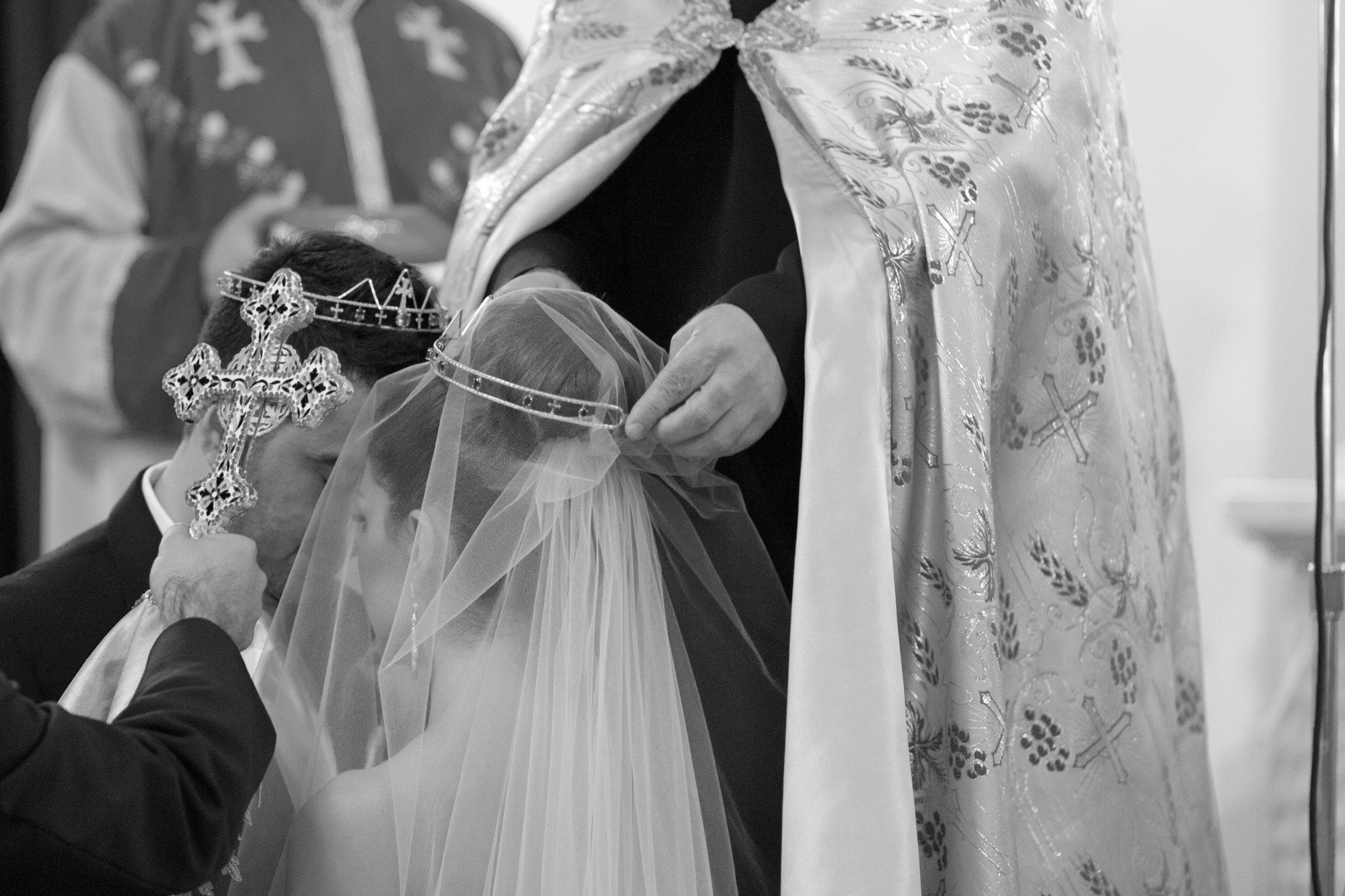 Groom and veiled bride during Catholic wedding ceremony