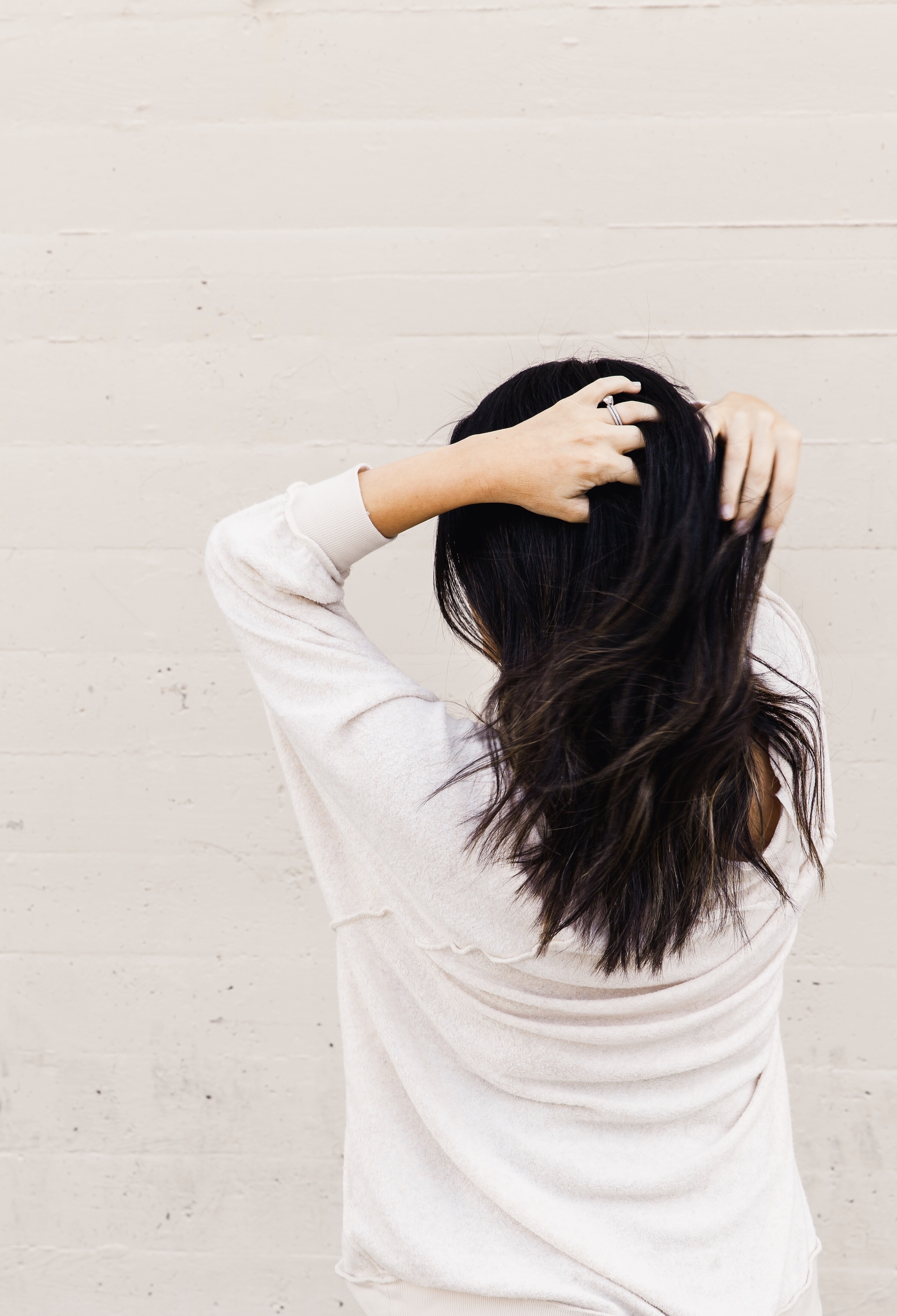 Picture of El Abad facing a neutral toned wall wearing a white sweater and running her hands through her dark hair.