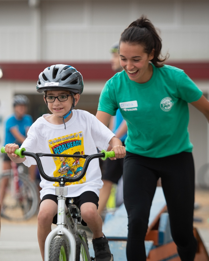 Female Pedalheads instructor in green tshirt helping a young boy with glasses learn to ride his bicycle.