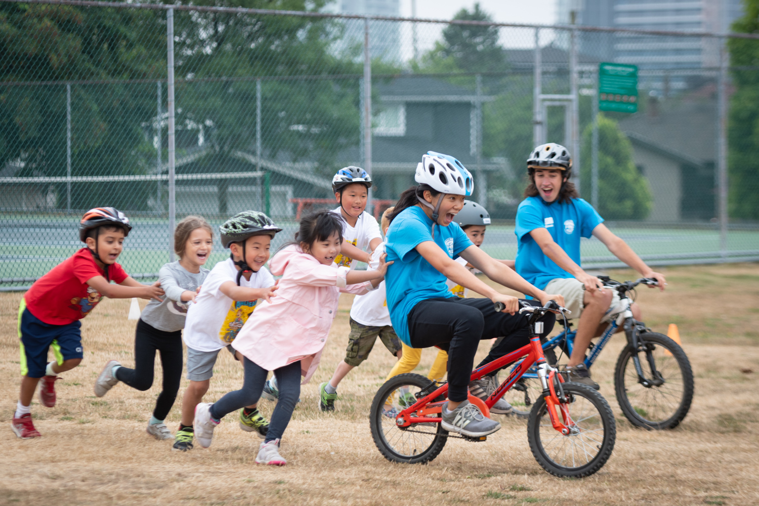 Children pushing Pedalheads instructors on bicycles, laughing as they race during this fun camp event.