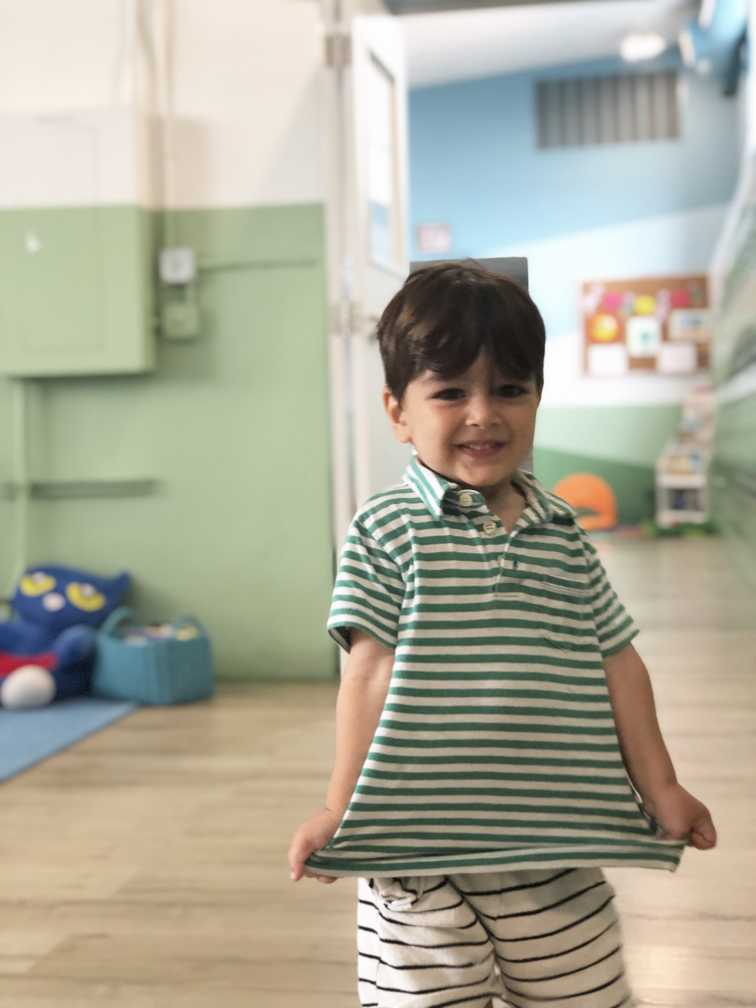 Ryan, son of Land of Mom founder El Abad, smiling and stretching his green and white striped polo shirt.