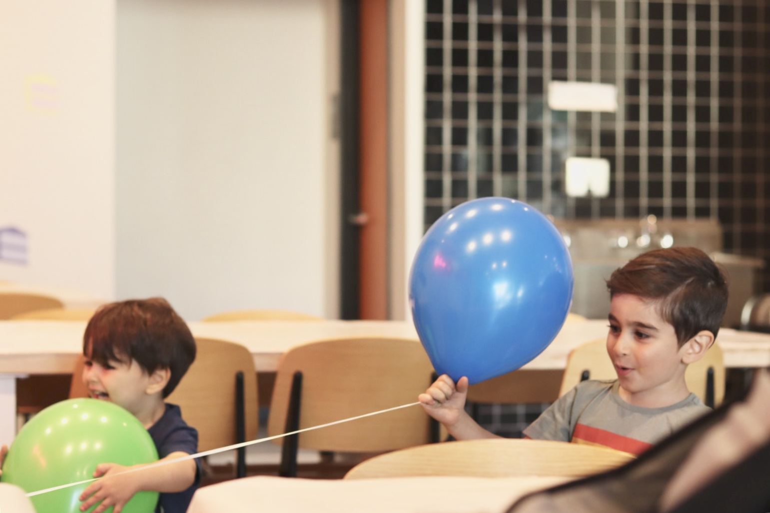 El Abad's sons Ryan (4 years old) and Leo (2 years old) playing with balloons. Land of Mom.