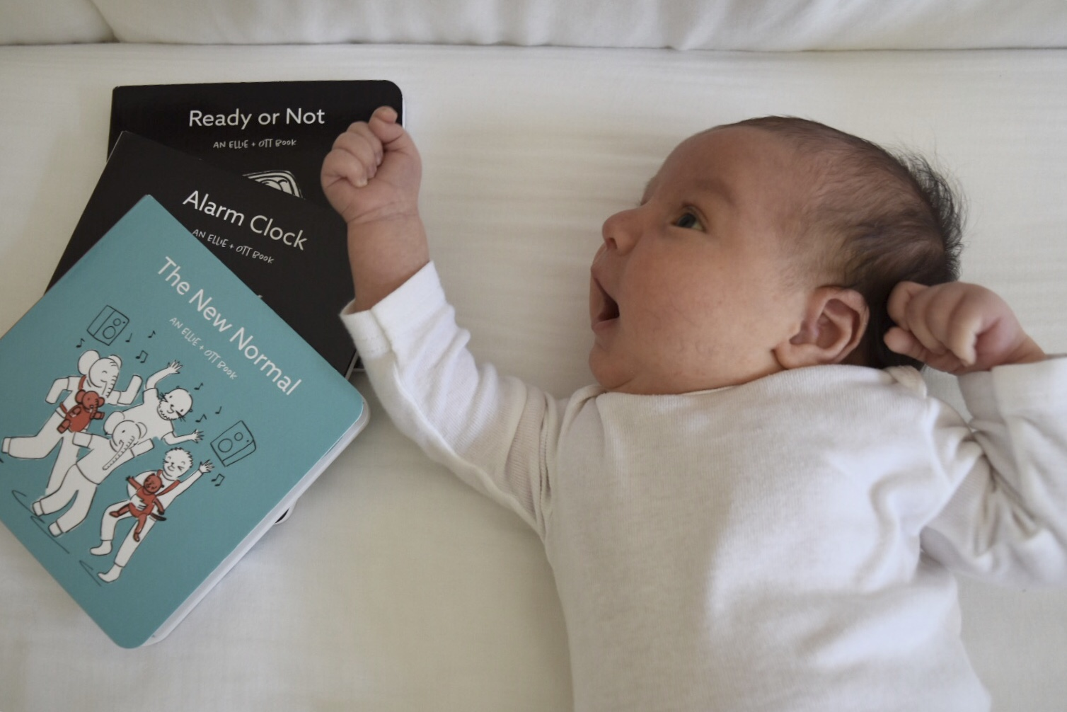 Little Max Gharibian snuggled up in a white onesie with his new board books from Ellie + Ott: Ready or Not, Alarm Clock, and The New Normal