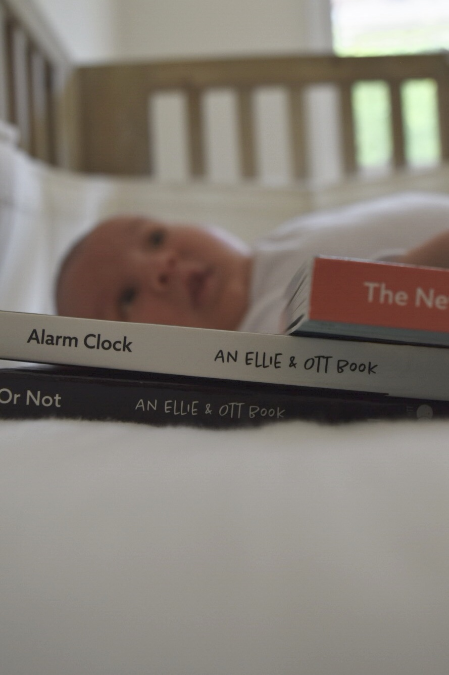 Little newborn boy Max Gharibian lying in his wooden crib with his new board books from Ellie + Ott: Ready or Not, Alarm Clock, and The New Normal
