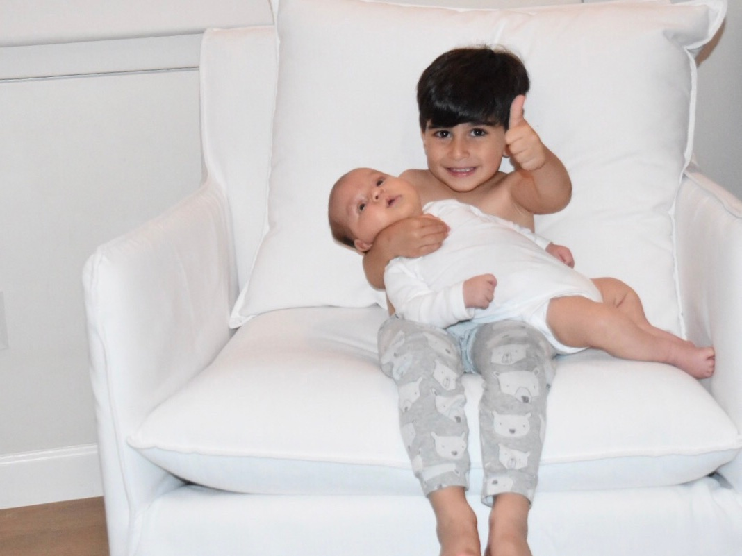 El's middle son Leo sitting on a white chair giving a thumbs up while holding newborn baby brother Max in his lap.