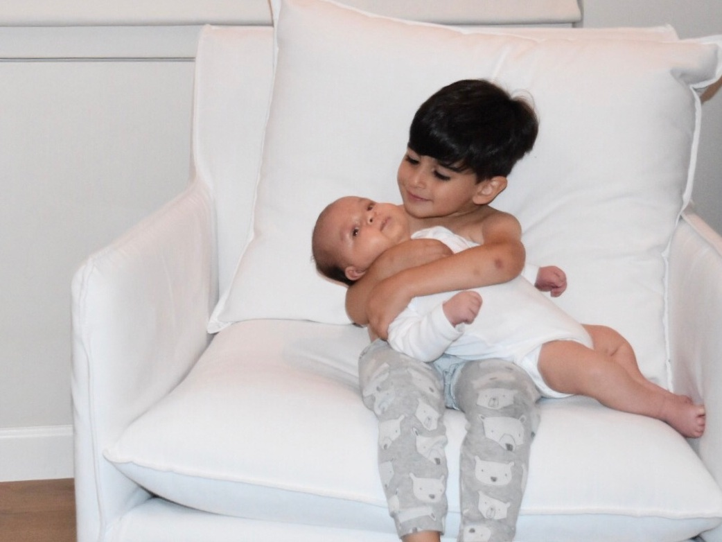 El's middle son Leo sitting on a white chair holding newborn baby brother Max