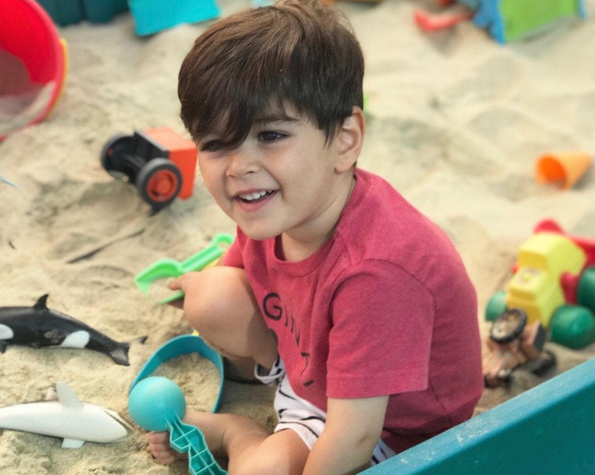 Leo playing in the sandbox, wearing his new Lucky + Me briefs