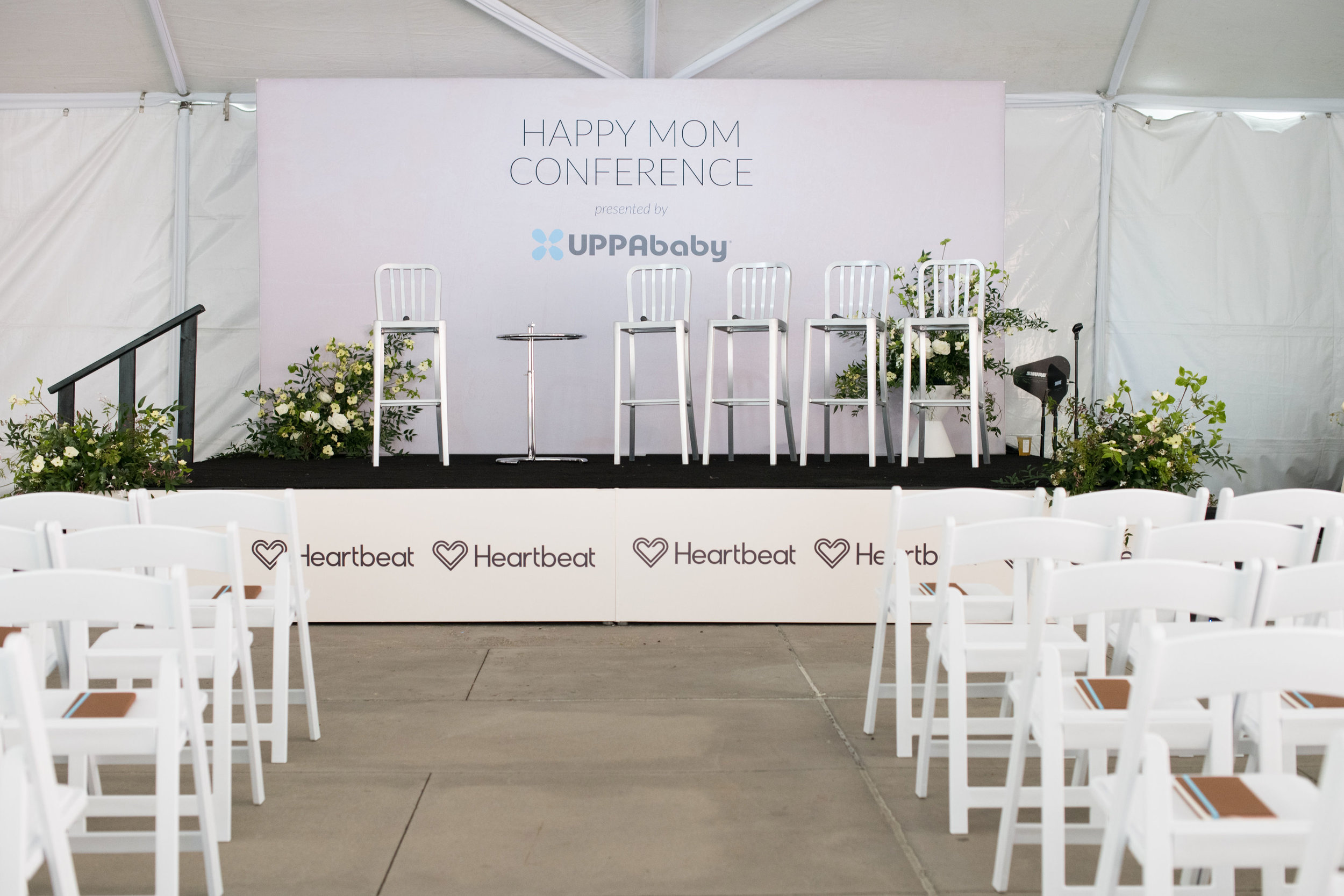 """View of the Happy Mom Conference 2019 stage from the center aisle. White chairs on either side with lovely leather notebooks on the seats are set up for each mama attending, while the Heartbeat sponsored stage is set with seats for panelists, minimalist white floral arrangements, and a """"Happy Mom Conference presented by UPPAbaby"""" backdrop."""