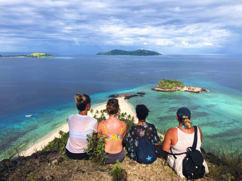 Friends and I sitting after a short hike on Castaway Island, looking out at the eminent blue of the coral reefs below us. Photo by Yanik Rozon.
