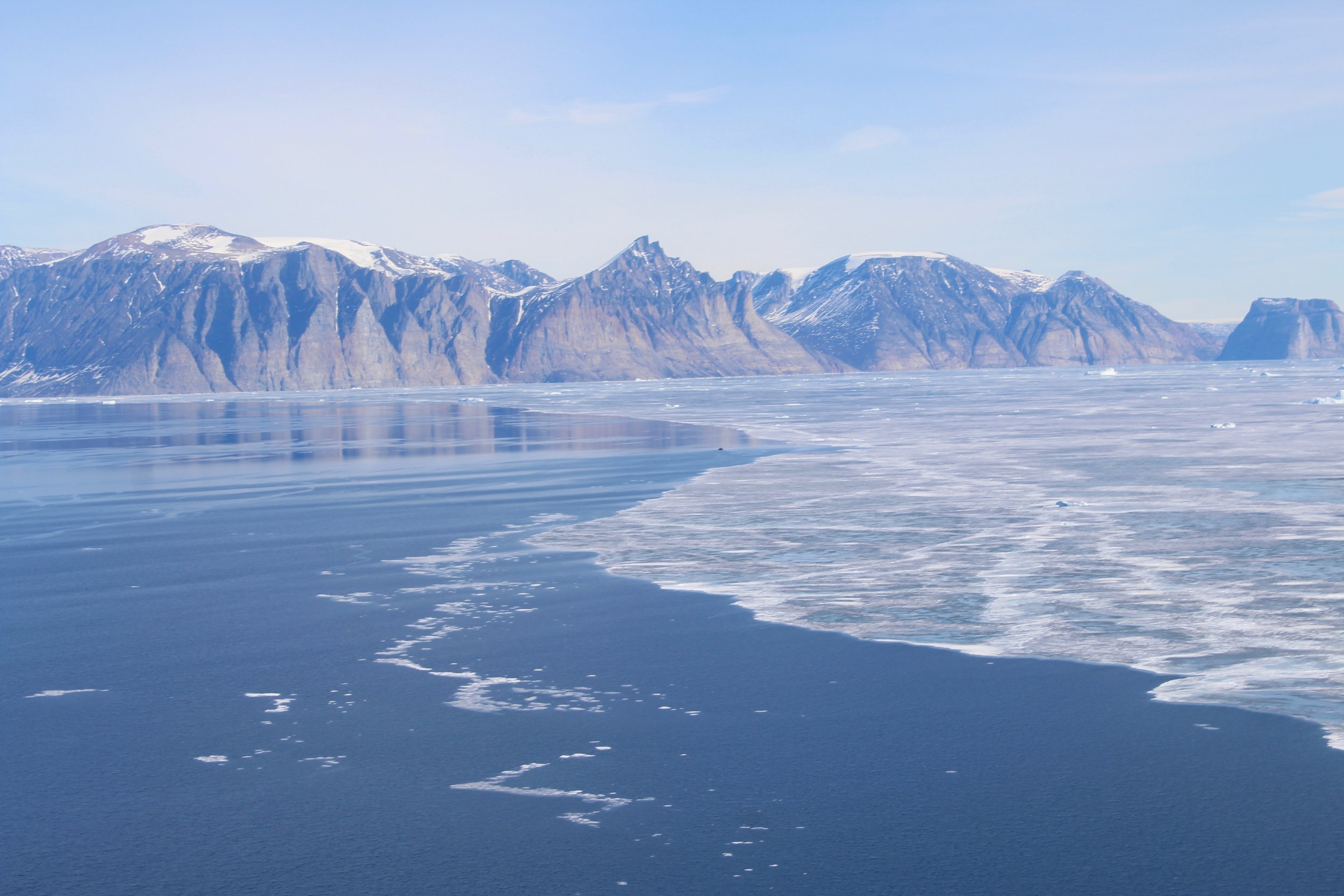 The shorefast ice edge in Uummannaq Fjord, viewed from a helicopter in May 2019