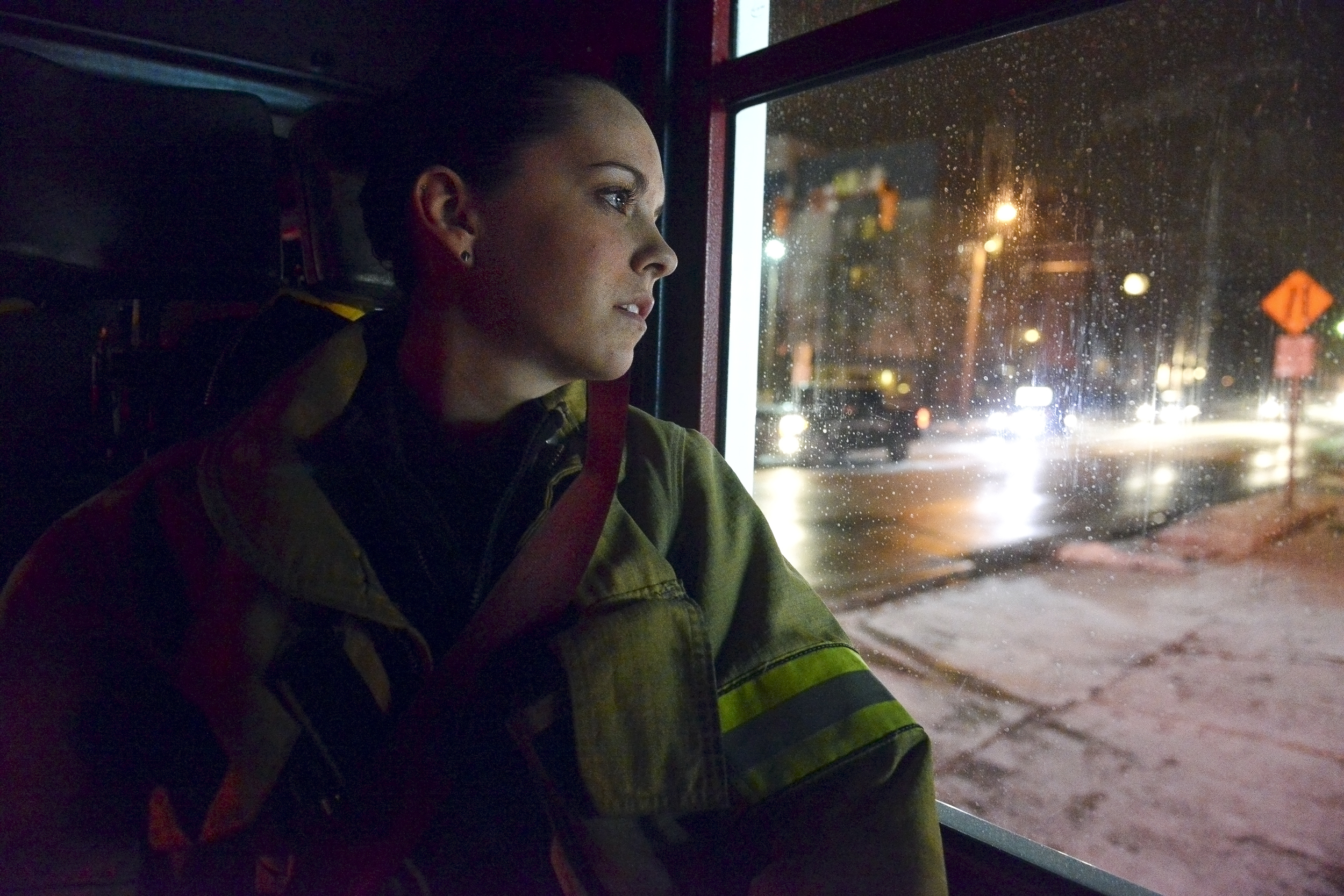 Ali Warren, a 20-year-old volunteer firefighter for the Alpha Fire Company, watches out the window of the fire engine as they arrive back to the station on South Atherton Street in State College, Pa. Warren, a State College local and self-published writer, has been volunteering for the company since she was 16.