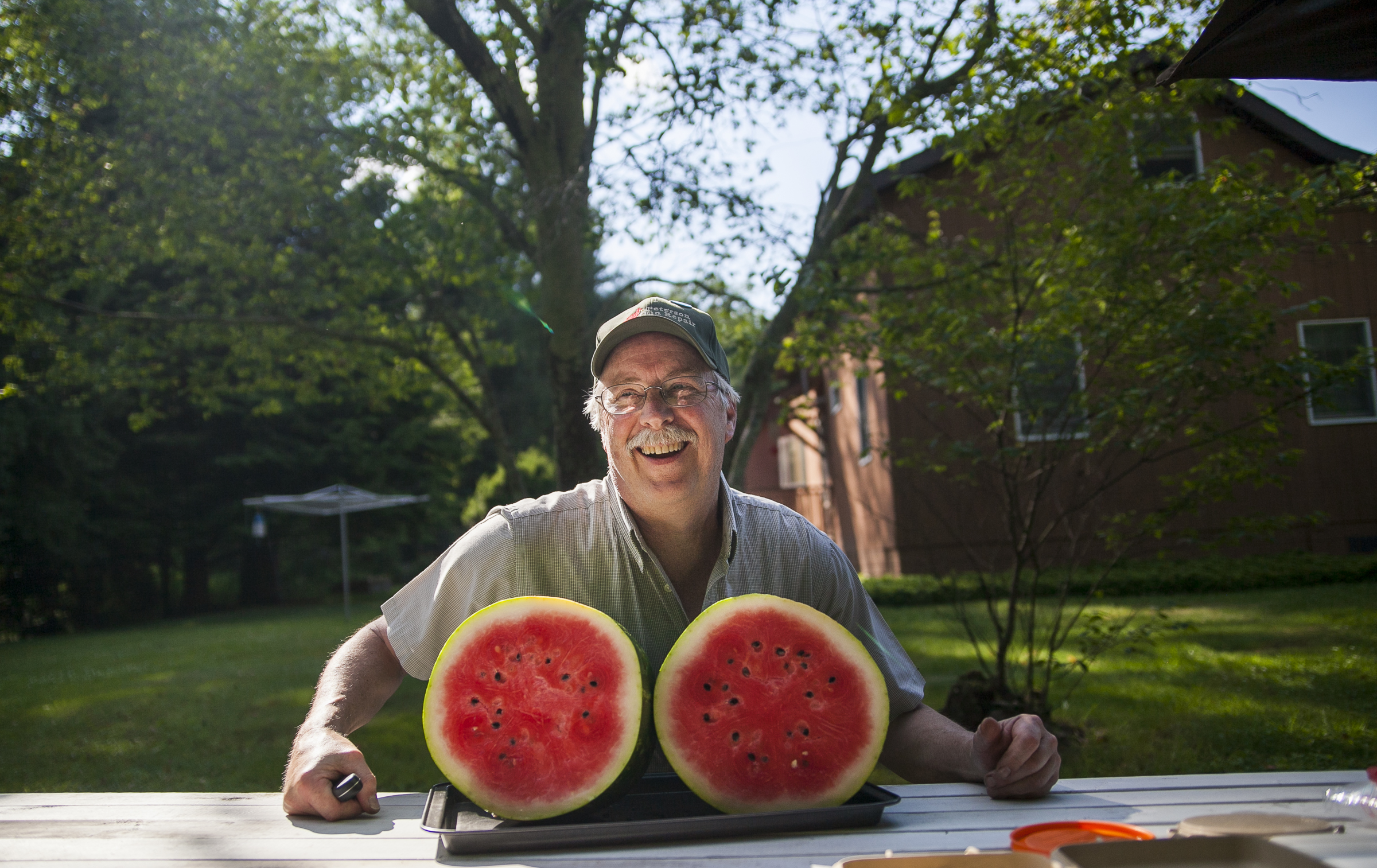 John Peterson poses with a watermelon he just chopped in half in Clarendon, Pa.