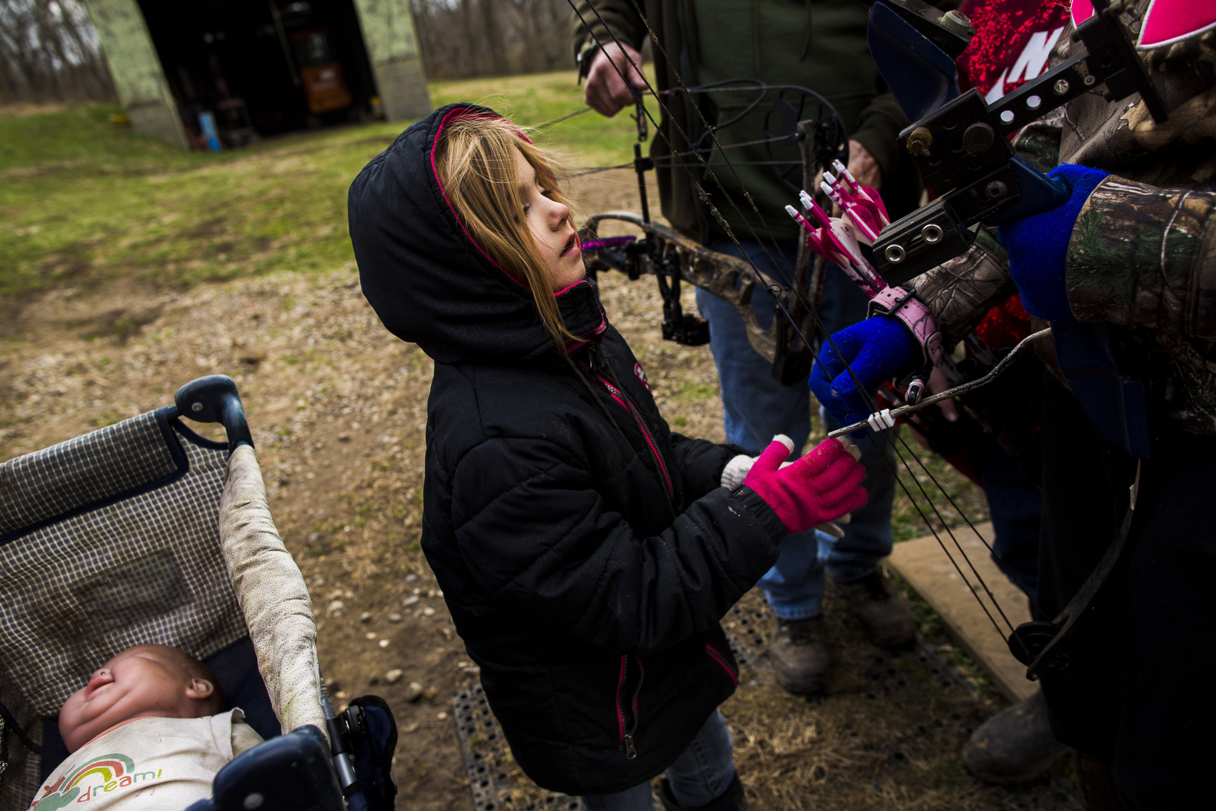 Emily takes a break from playing with baby doll to inspect her sisters's bow and arrows.