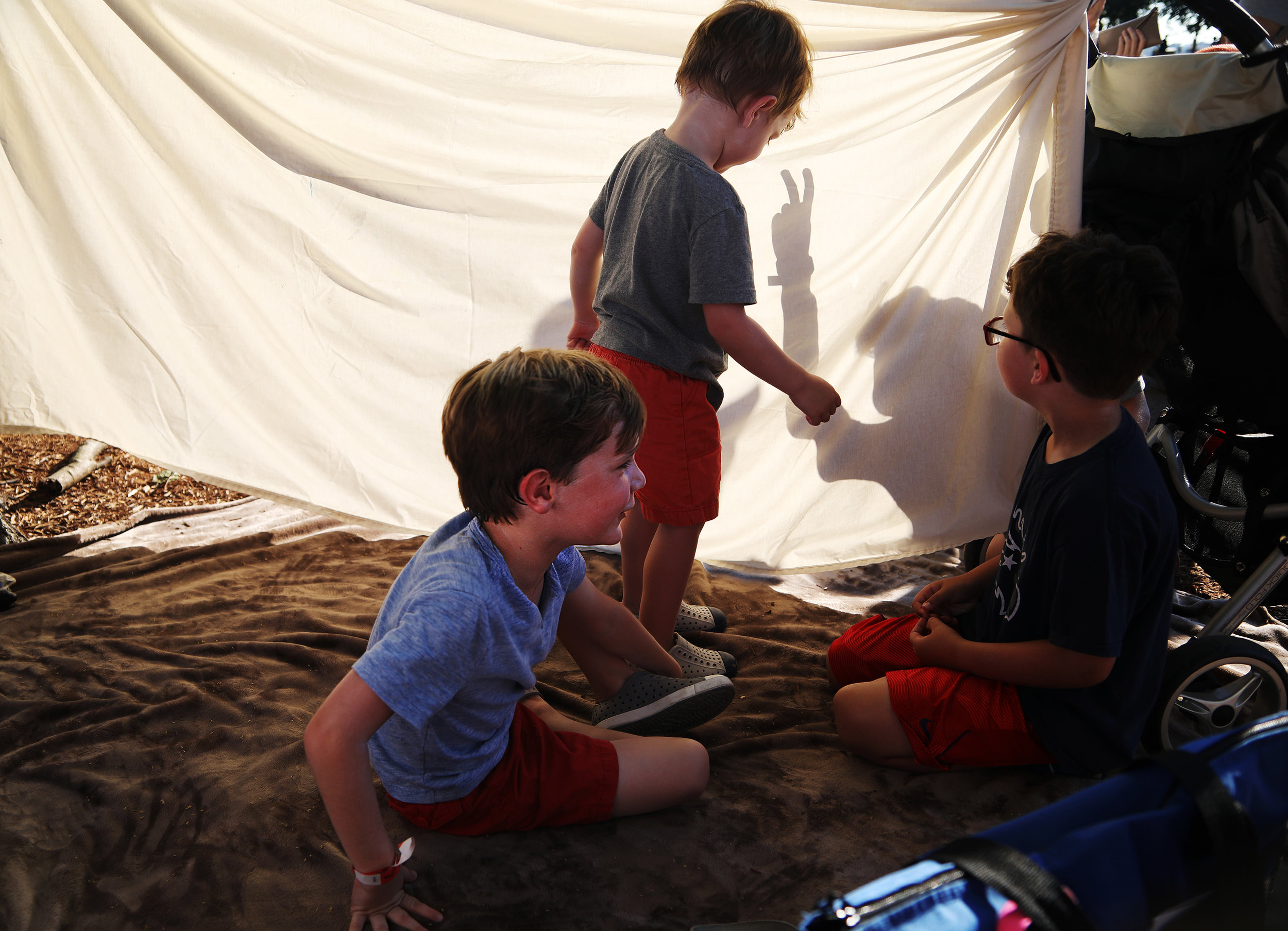 Charlie Groom throws shadows on a sheet while playing with his cousins Owen, Leo and Colin (left to right).