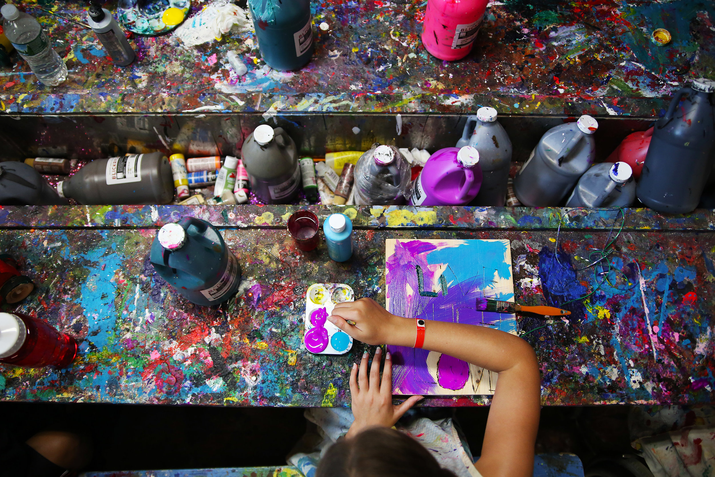 Sophie paints on a canvas at the Hole in the Wall Gang Camp. Created by Paul Newman in 1988, Hole in the Wall Gang Camp is dedicated to providing a week long camp experience to seriously ill children and their families.