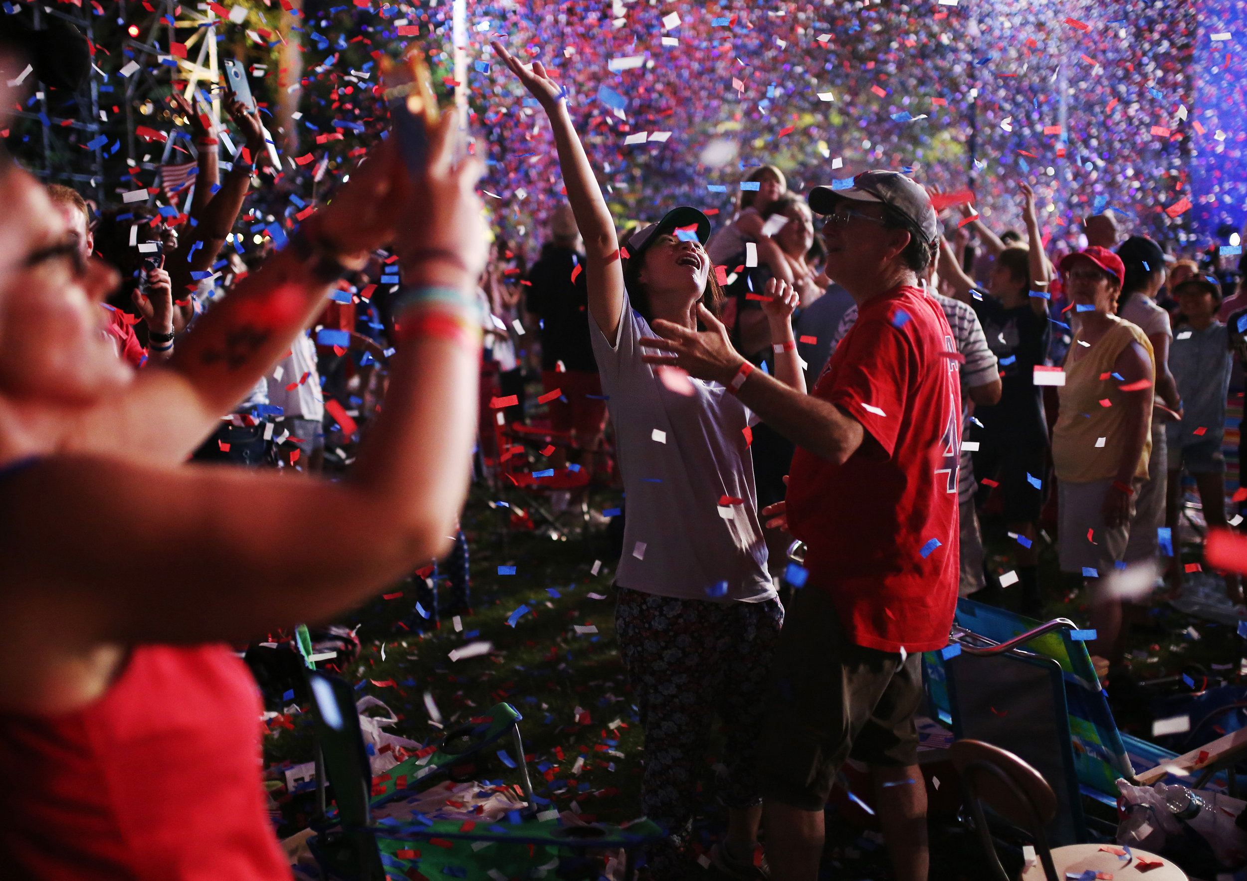 "People celebrate in the confetti during the Boston Pops Fireworks Spectacular. Despite the heat; ""a large crowd came out to celebrate one of the country's largest and oldest public Fourth-of-July events that took place on the Esplanade."