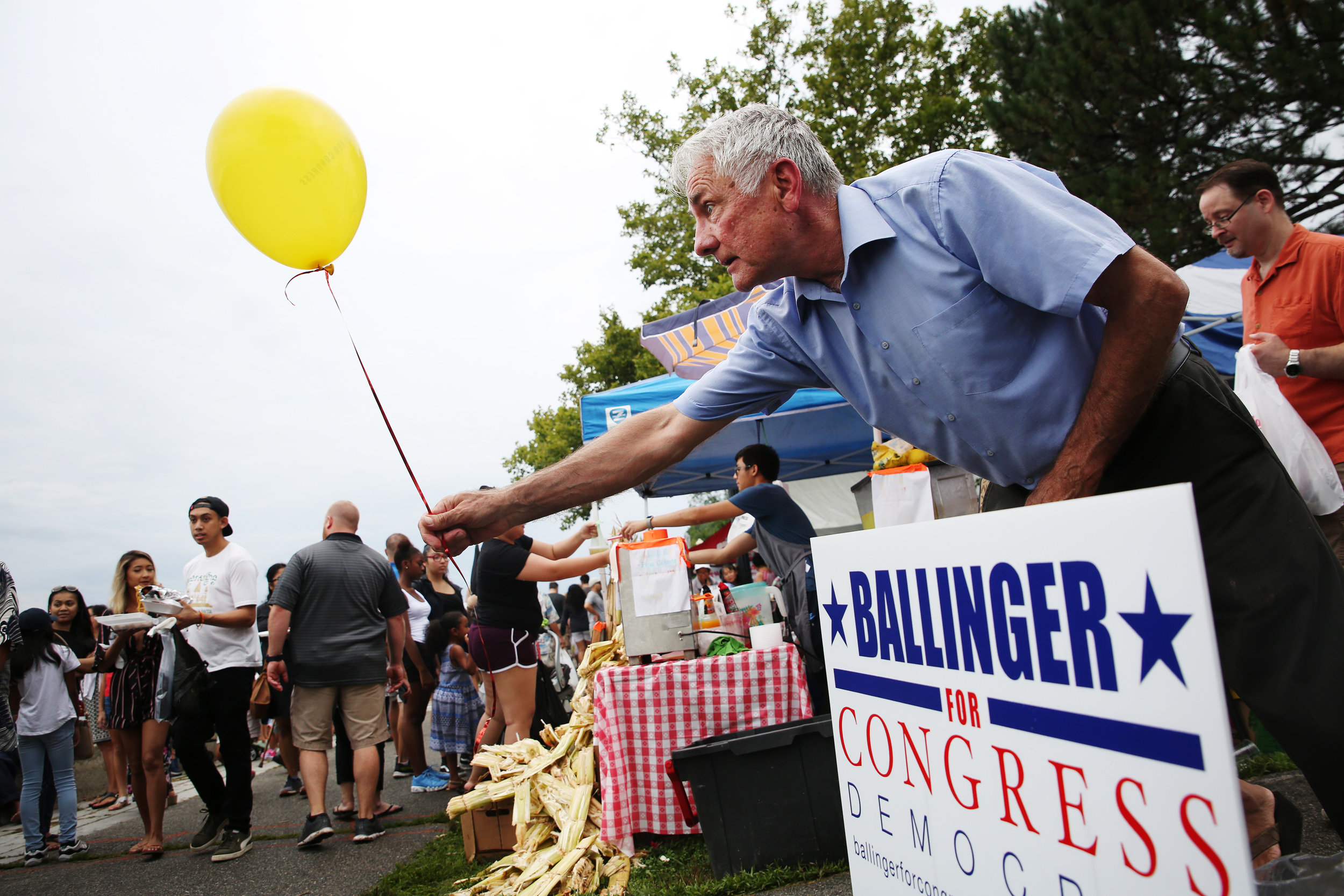 Labor advocate Jeff Ballinger hands out balloons to people at the Lowell Southeast Asian Water Festival. Ballinger is one of 10 democratic candidates running to represent the people of Massachusetts' 3rd District in U.S. Congress.