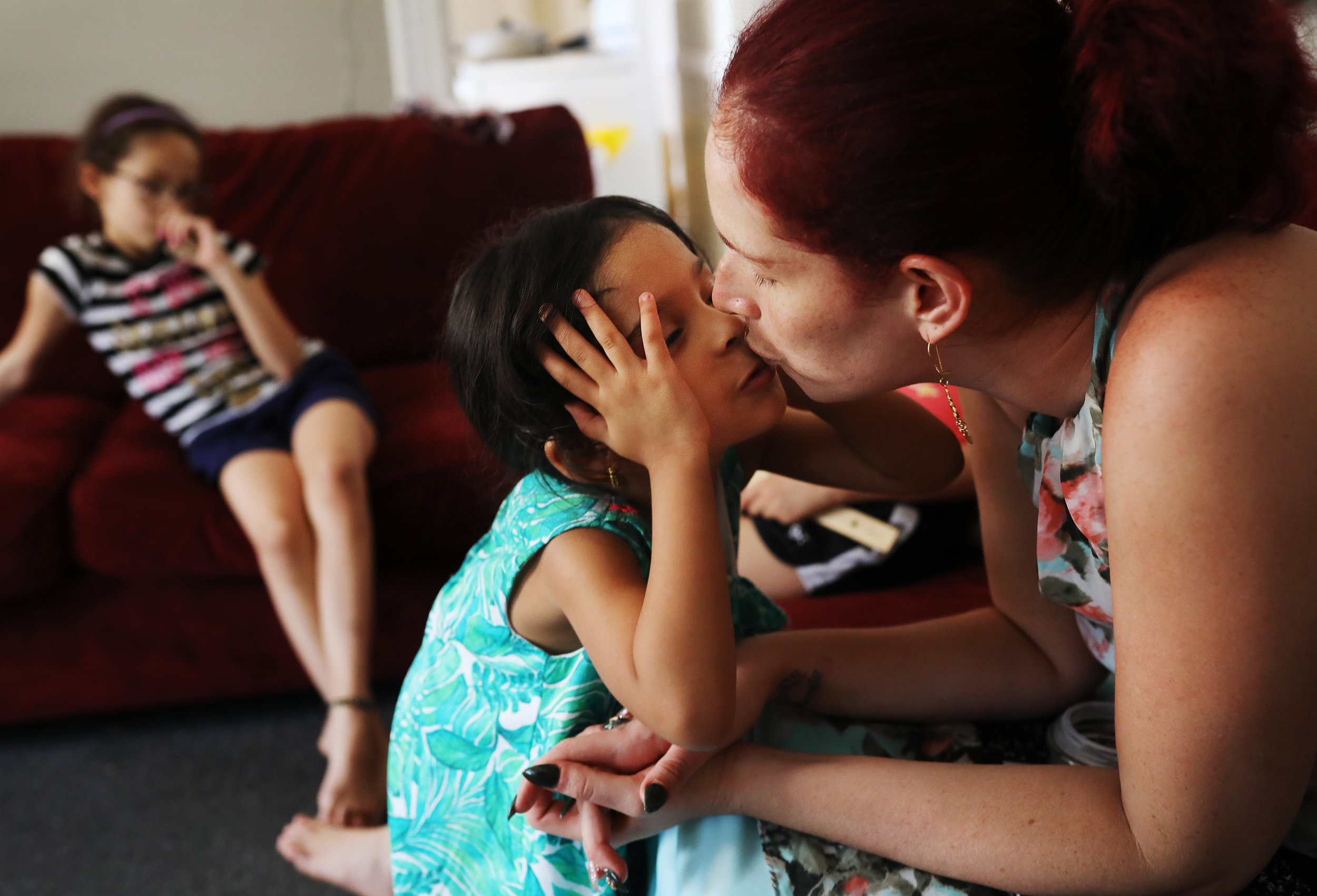 Gennie Garcia, right, kisses her daughter Getzaynie, 4-years-old, while they spend time in their friend's apartment. Gennie was illegally subletting from a friend after moving from Puerto Rica after Hurricane Maria. The landlord has demanded she be out by July 1. She didn't qualify for FEMA's TSA program due to a miscommunication about her family's home on the island. Today she's working to figure out where she's going to go next.