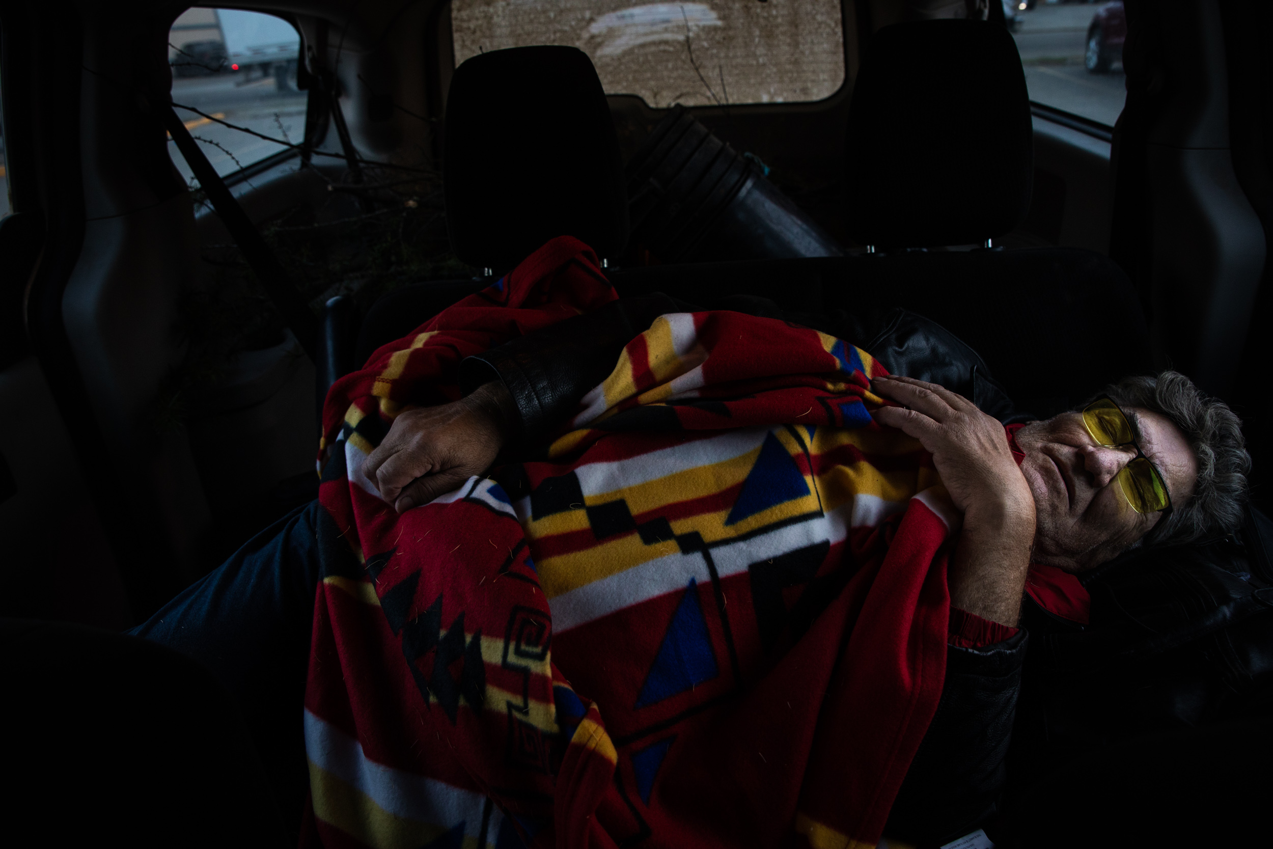 "Russell Willier, a Cree medicine man, rests in the back of his van after cutting plants to make Thunder Medicine. ""If this doesn't work, I have four months left,"" he said. Russell is battling cancer that started in his bladder, but has spread throughout other parts of his body. After doctoring himself through his initial fight with bladder cancer, Russell is now seeking westernized treatments alongside his medicine, but refuses to use radiation or chemotherapy."