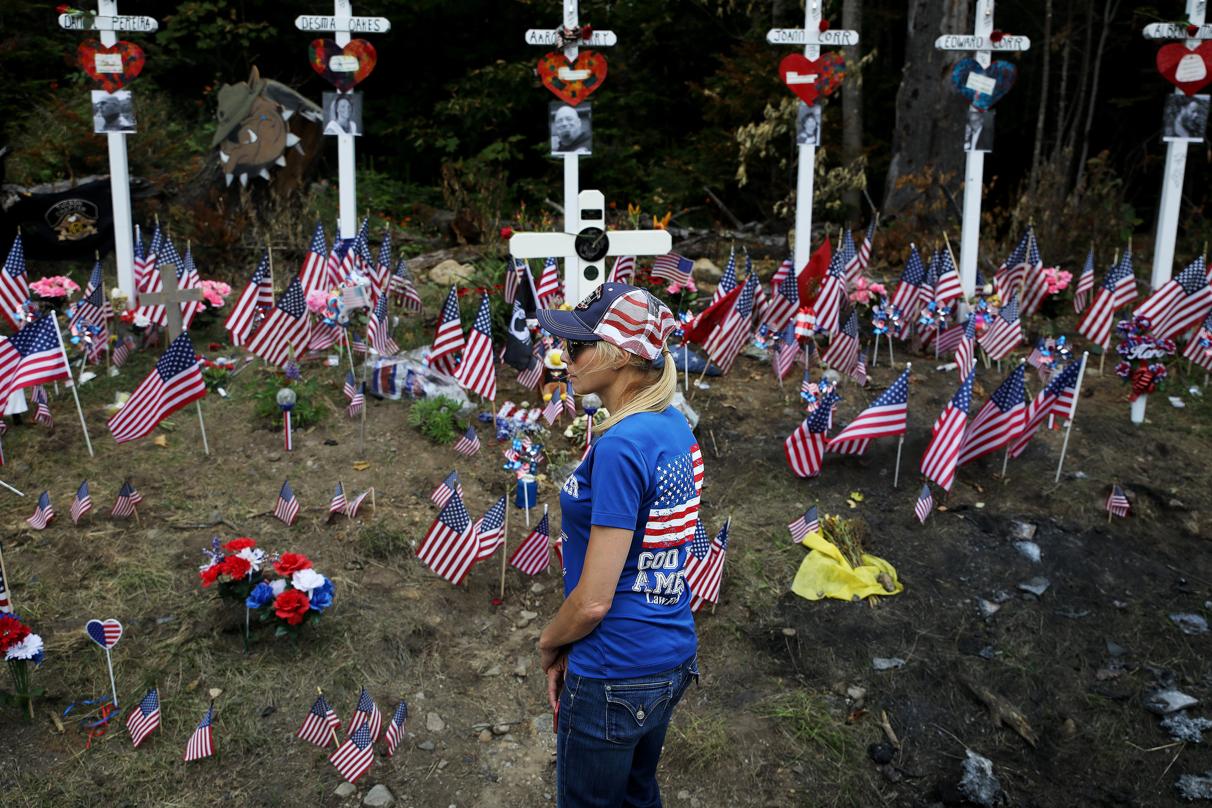 Fran Haash, of Tampa, Florida, looks at the memorial site where seven bikers recently lost their lives. Thousands of motorcyclists from all over New England rode together and convened at the crash site where seven motorcyclists were killed in a collision with a pickup truck.