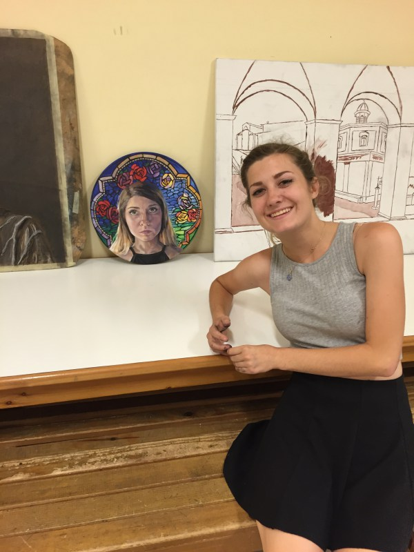 Jenna sits with her completed oil painting as the visual arts class hosts a critique. She will be presenting the progression of her oil painting, explaining her challenges and successes through the process of painting this realistic self-portrait with a stain glass window background inspired by Spoleto's churches.