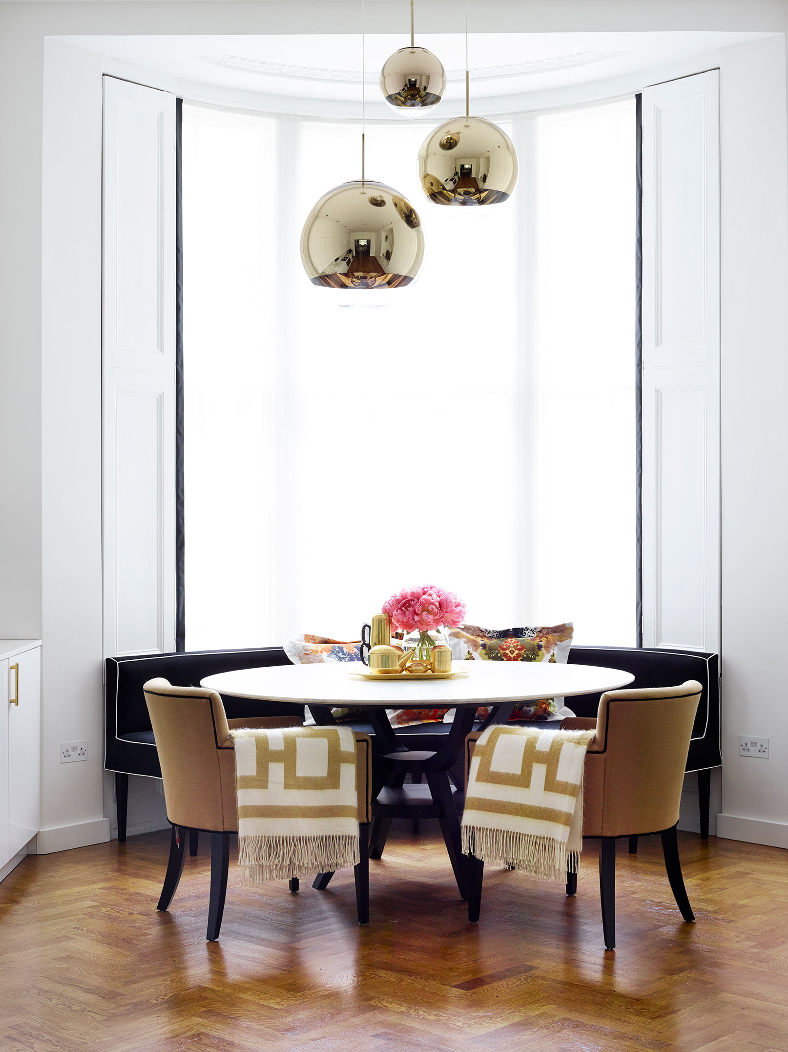 The curved black banquette piped in cream was custom made to Lynn's specifications by designer Raj Sharma.  Tom Dixon 's Mirror Ball pendant lights add sheen, while  Jonathan Adler 's Nixon alpaca throws introduce a luxurious note.