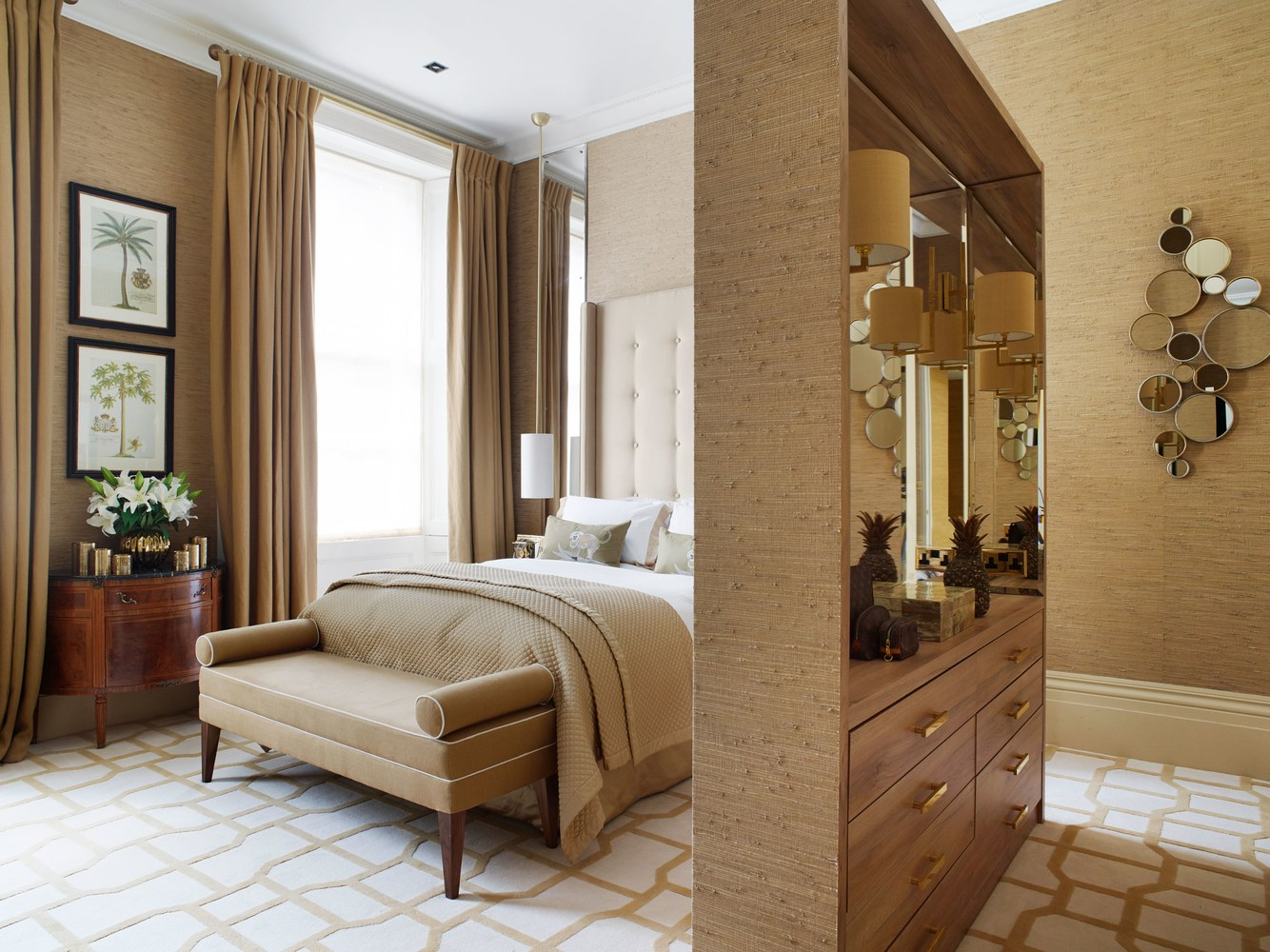 Inspired by her favorite London hotels, the master bedroom combines functionality and old-school glamour with a palette of restful caramels and golds. A partially mirrored wall divider acts as a handy storage and dressing area.