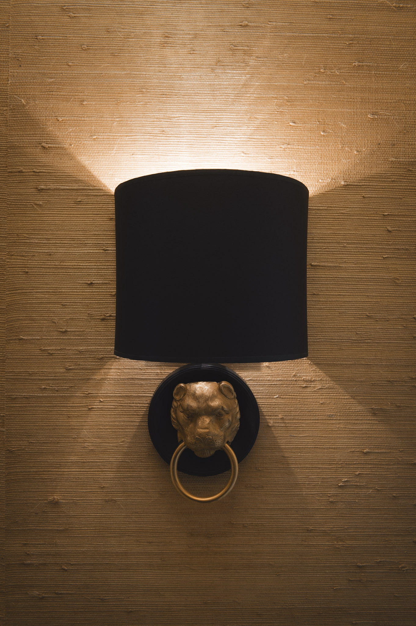 Vaughan 's Lion Head wall lights add a hint of glamour, while a black metal pendant introduces a graphic note.Walls are lined with Pearl River Jute from  Thibaut 's Grasscloth collection.