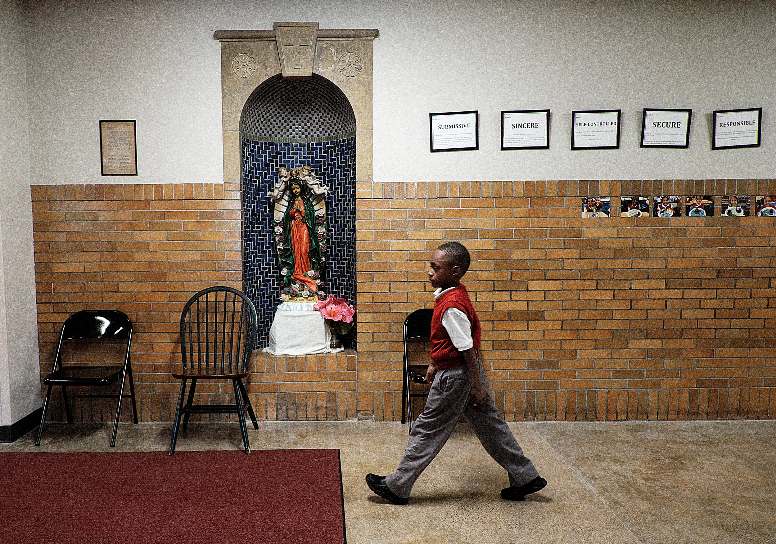 First-grader Mario Williams walks down the main hall at Ascension Catholic School, where expectations and values are posted on the wall.  Photo by David Pierini