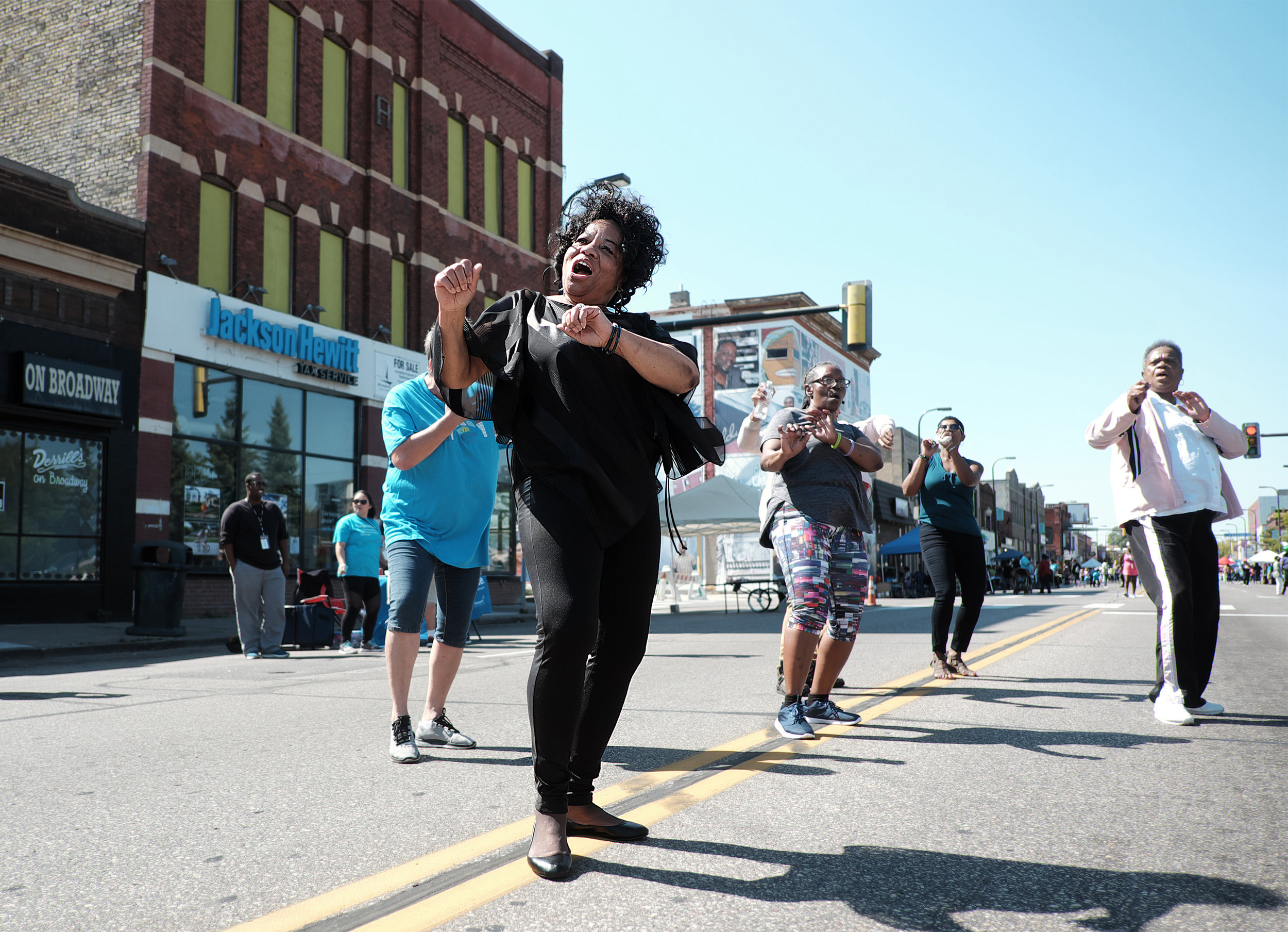 Albretta Safford dances with friends from the Heritage Park YMCA on West Broadway for Open Streets.