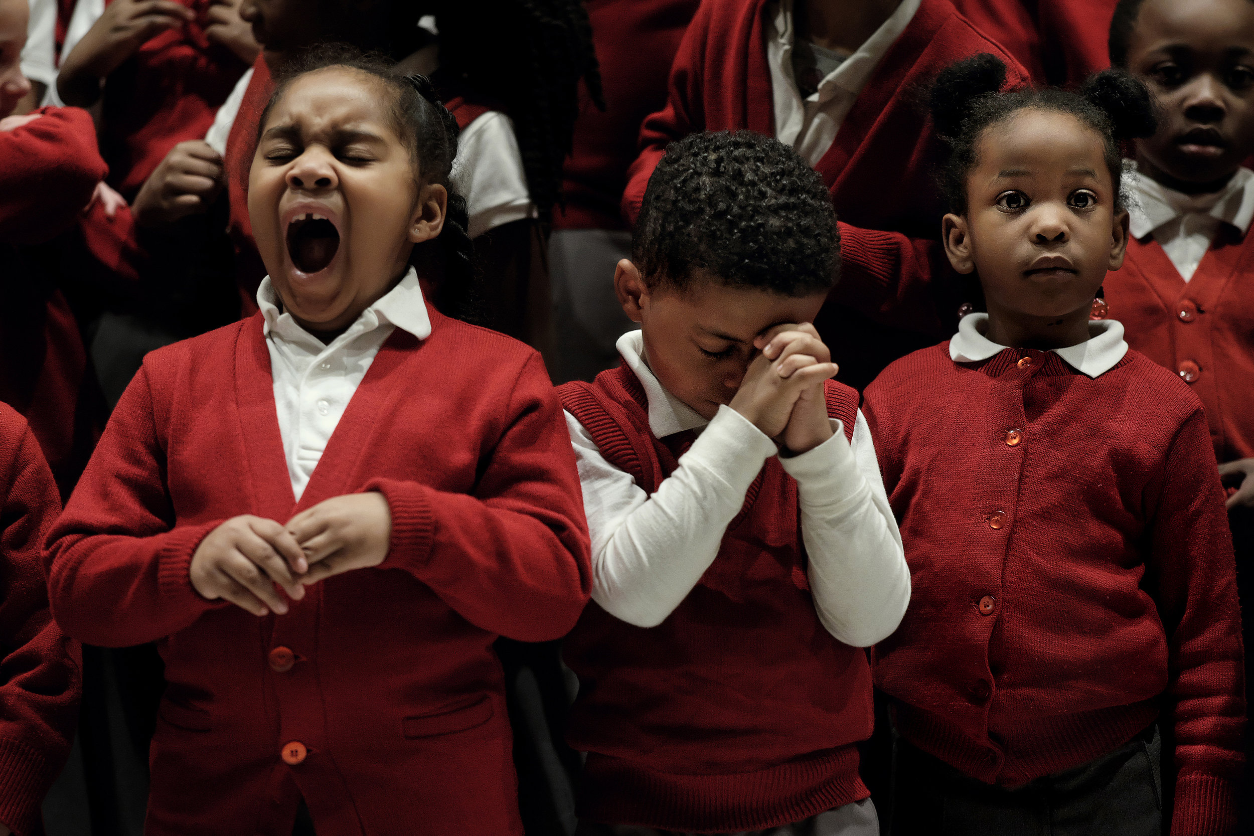 Kindergarteners Aniyah Dobbins-Bailey, Jonas Dixon and Tahiry Collier fidget during a closing prayer at Ascension School's annual Christmas program in December. The eighth grade performed a musical play about the birth of Christ titled  Josie and the Jinglicious Dream Lamp in front of family and friends who packed the church. The other grades, like kindergarten classes, were part of the chorus.
