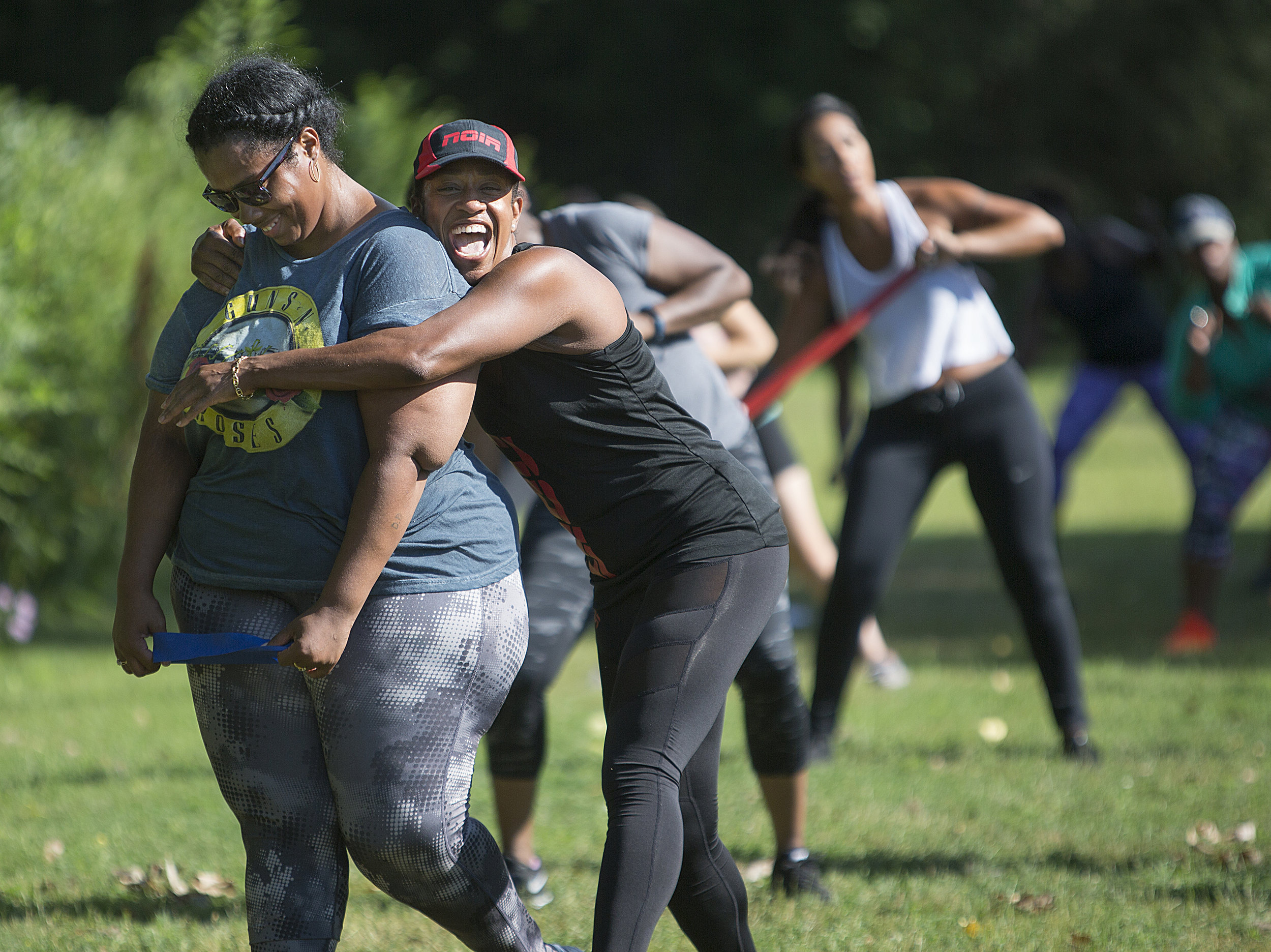 Val Fleurantin of Noir Elite Fitness hugs a class participant at her Jammin' in the Parks pop-up fitness event in July. Fleurantin and her business partner Chaz Sandifer seek to support black women to live healthier lives. In 2018 they plan to open their own gym at North High School.