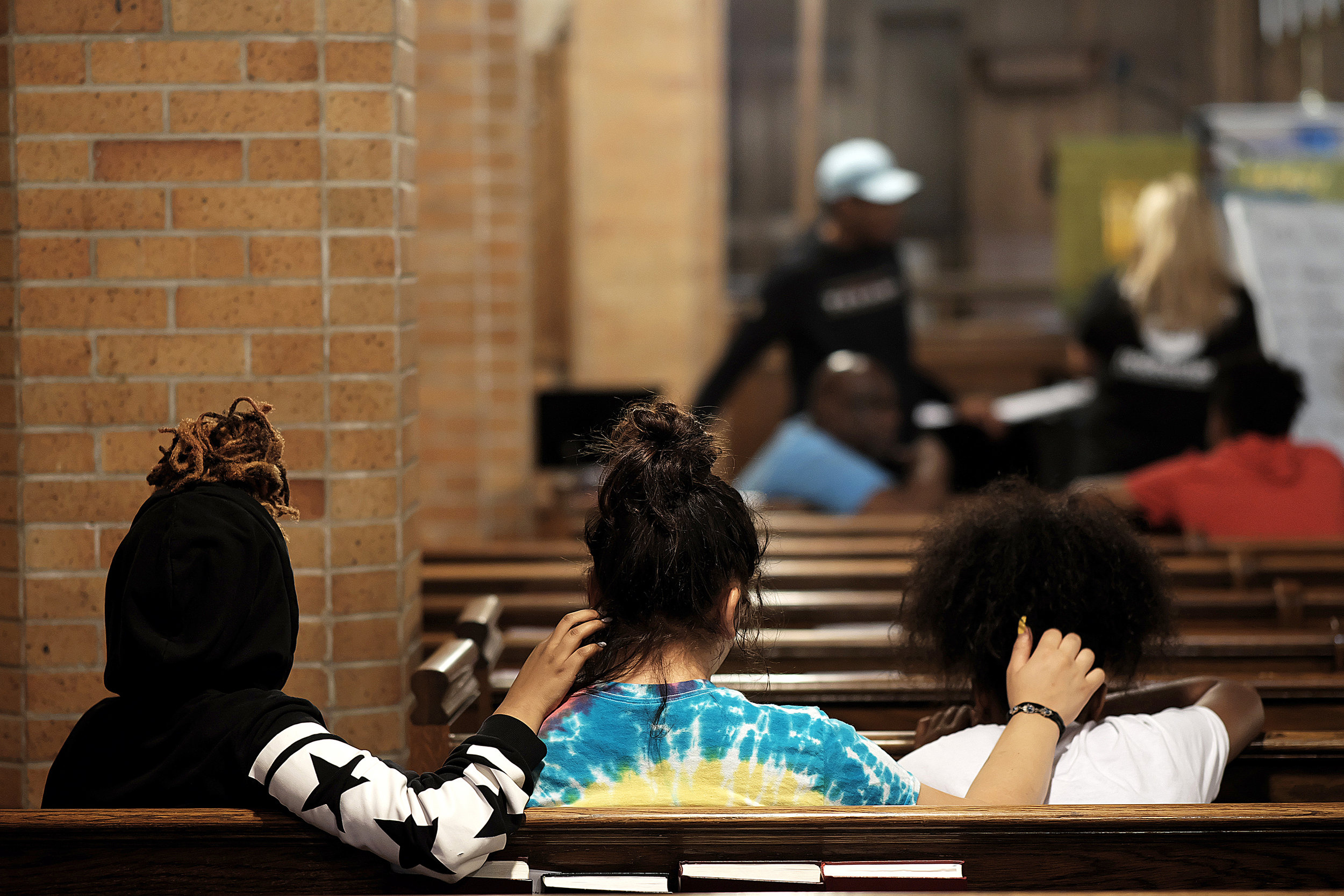 Three girls sit close while listening to music during a summer block party at Redeemer Lutheran Church.