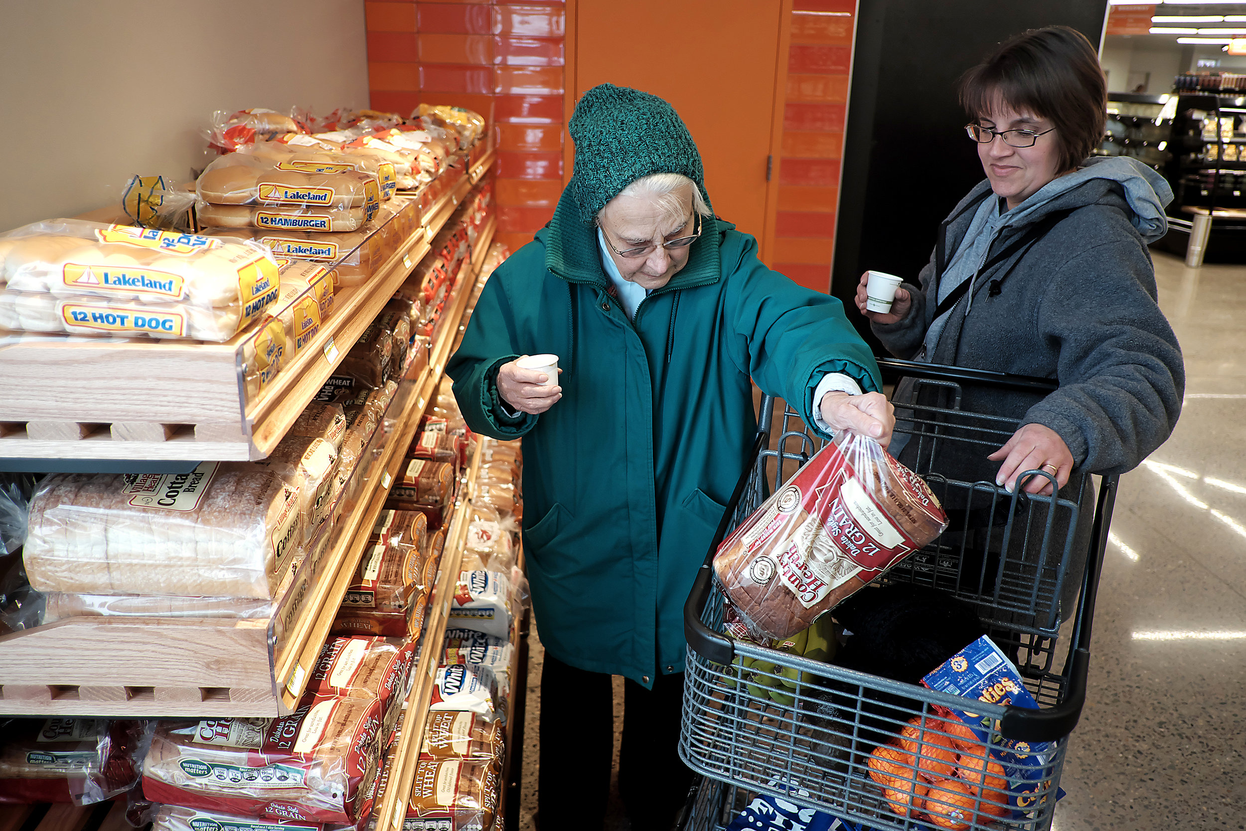 Ursula Armstrong, left, picks out a loaf of bread while shopping with her daughter, Heidi Temple, during the grand opening of North Market, the new nonprofit grocery store on 44th and Humboldt Avenues N in December.