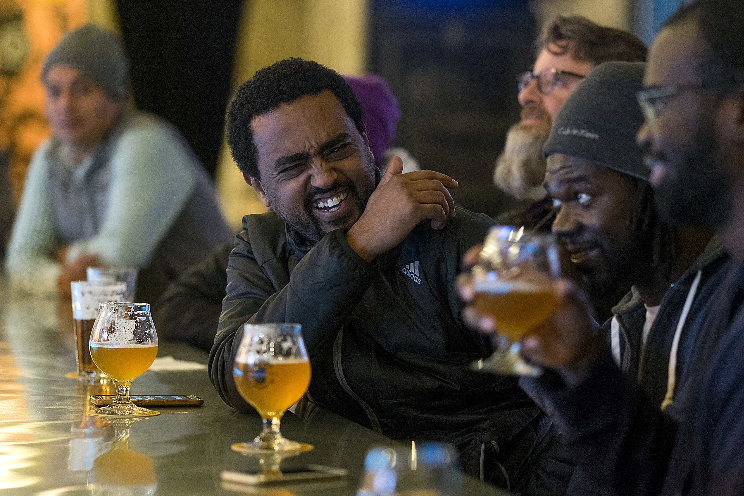 Yoni Debesai, left, Bobby Pyne and Seun Adenusa clinked glasses in a toast as they enjoyed the beer and friendship on a recent Friday night.