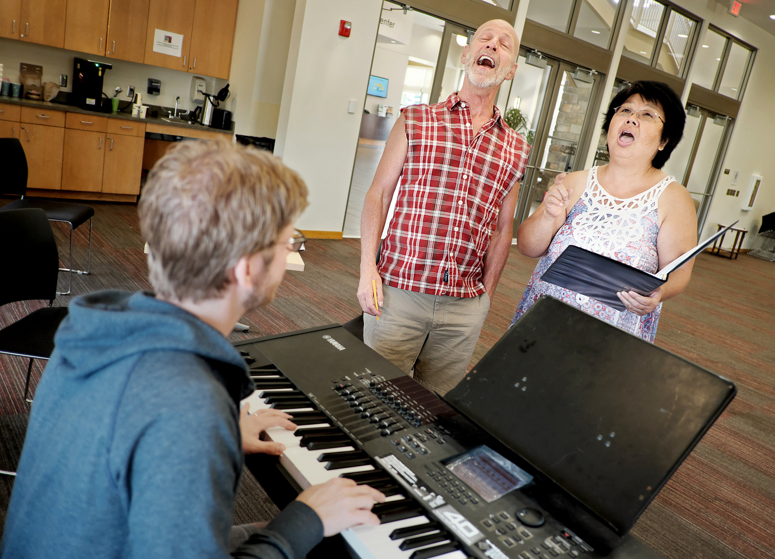 """Twin Cities' premier senior rock group """"Alive & Kickin"""" artistic director Michael Ferrell, center, helps Agnes Chik-Fufa belt out a song during an audition for the group. Afterwards, Ferrell told music director Jason Hansen, left, """"We've got a new rocker and she's gonna be good."""" The group meets at the Cora McCorvey Health and Wellness Center each Monday."""